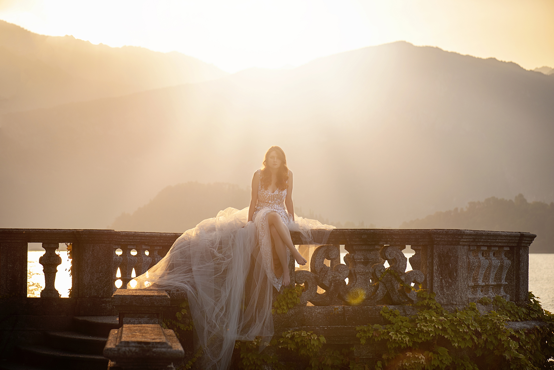 Bride sitting on stone ledge in front of mountains and lake Como in Italy with sunrising behind her