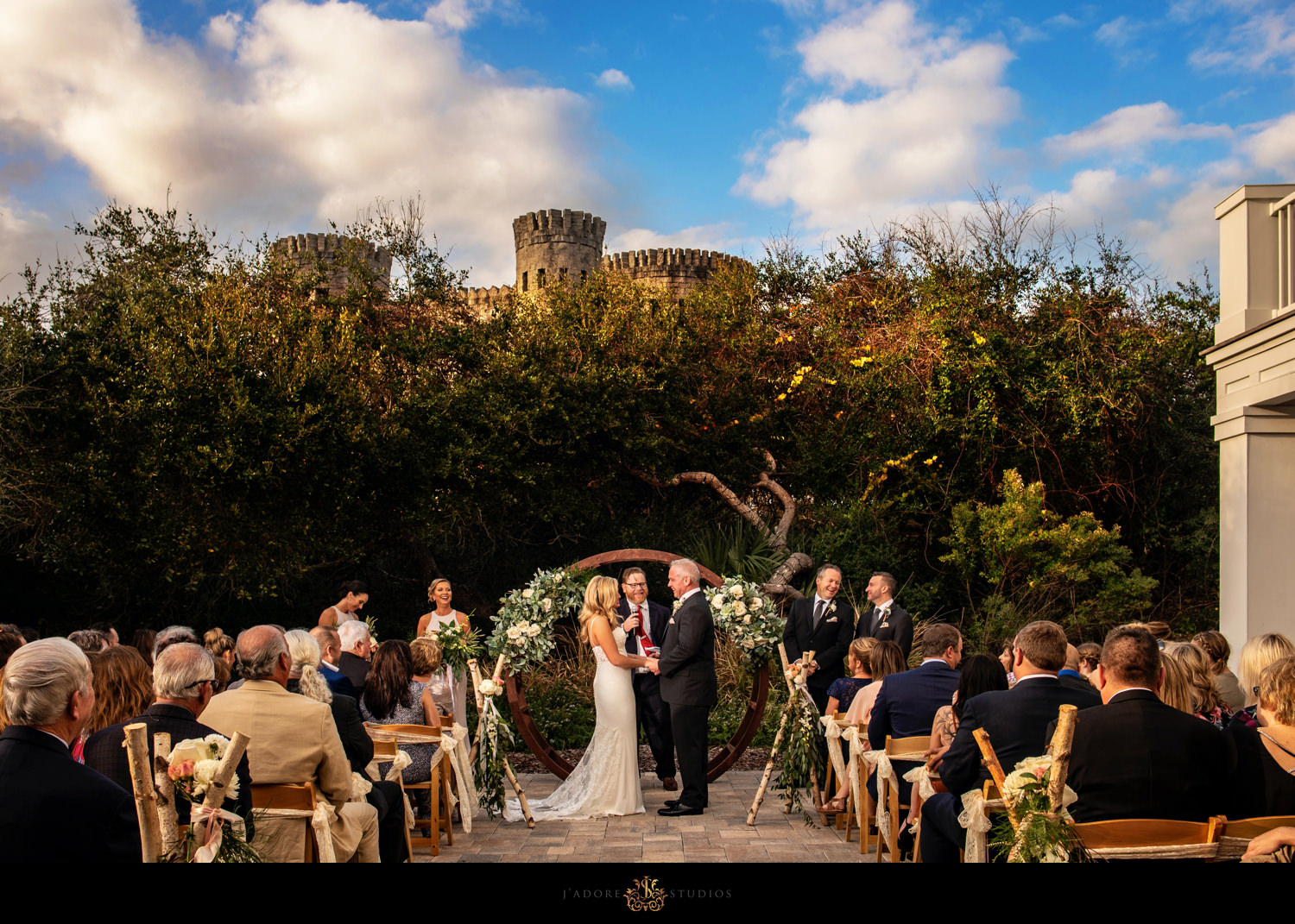 Wide angle ceremony photo.  Castle is int the background.  Blue sky