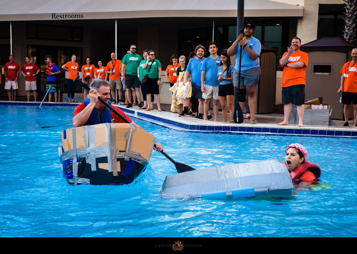 Team building event - Two colleagues in pool on cardboard boats