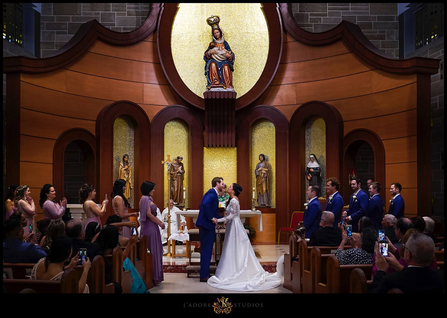 Couple about to have their first kiss in church with clapping friends and family at Our Lady of La Leche in Saint Augustine Florida
