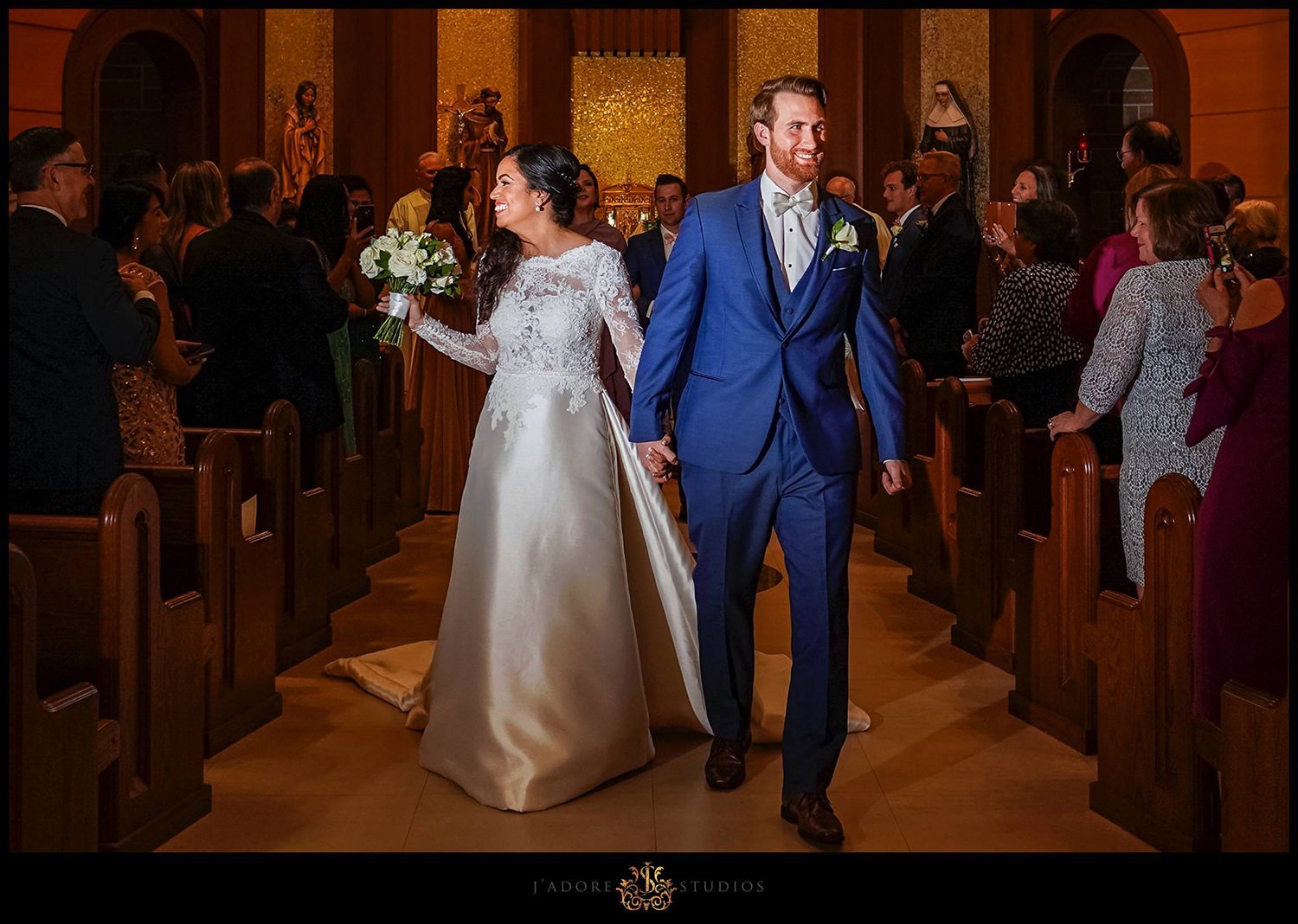 Couple walking down the aisle happy and greeting guests at Our Lady of la Leche in Saint Augustine Florida