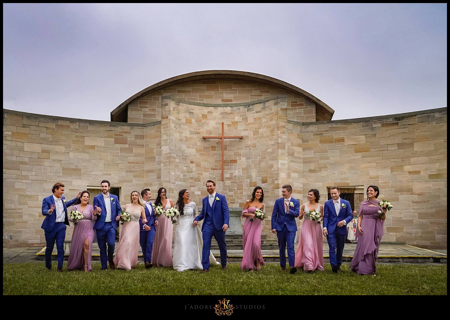 Bridal party walking towards the camera laughing dancing and having fun in front of a gloomy sky at Our Lady of la Leche in Saint Augustine Florida