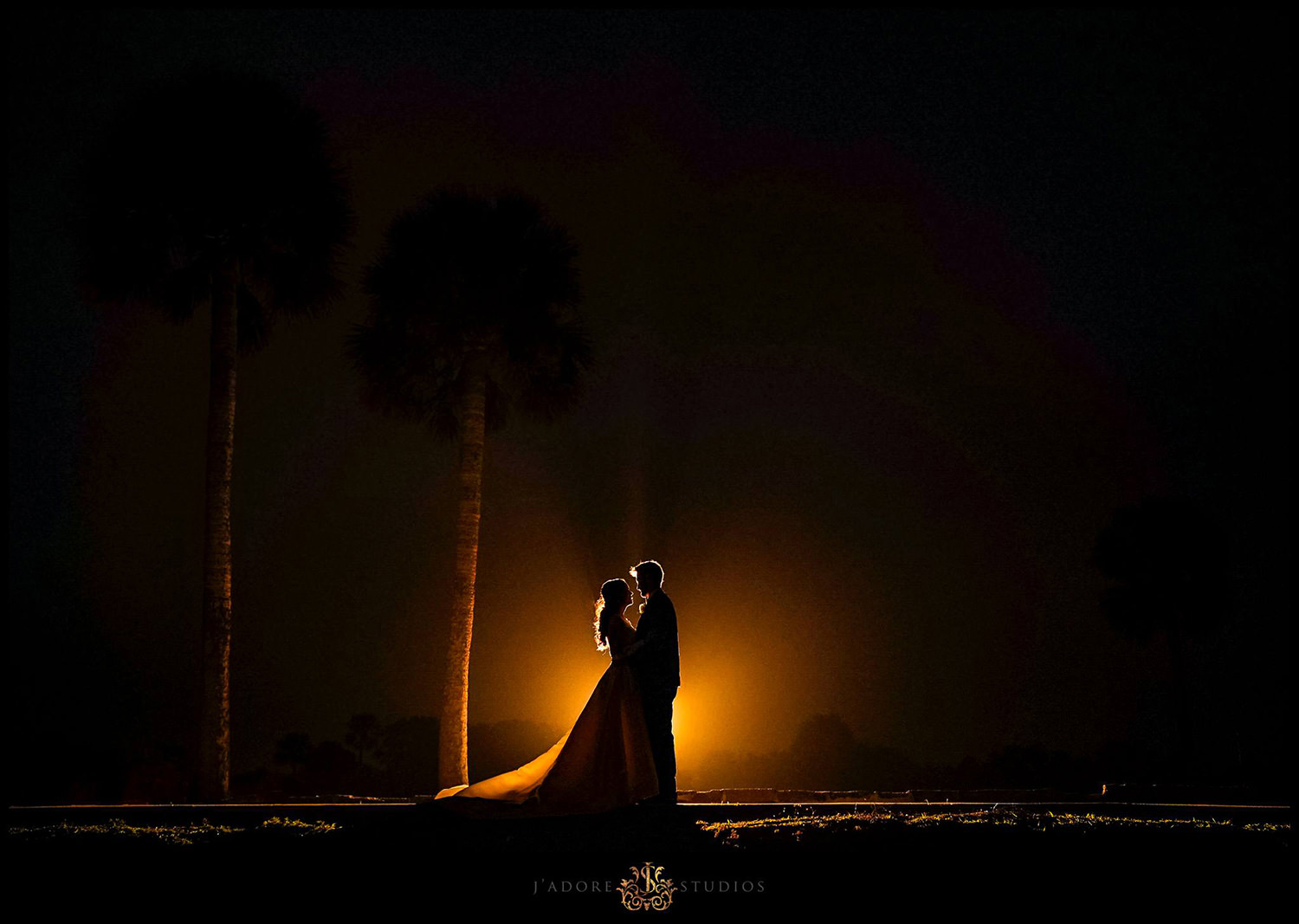Silhouette photo of bride and groom with palm trees and orange setting sun created with flash at the Treasury on the Plaza in Saint Augustine Florida