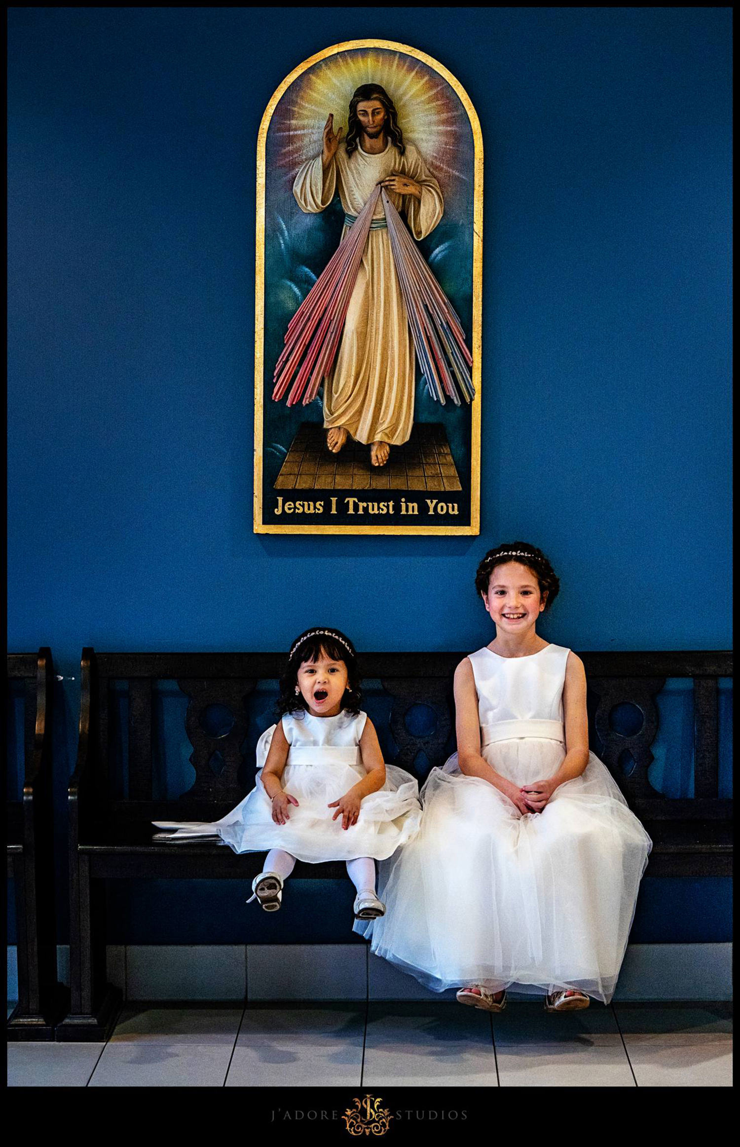 Two flower girls sitting below a portrait of Jesus on bench in front of a blue wall at Our Lady of La Leche in Saint Augustine Florida