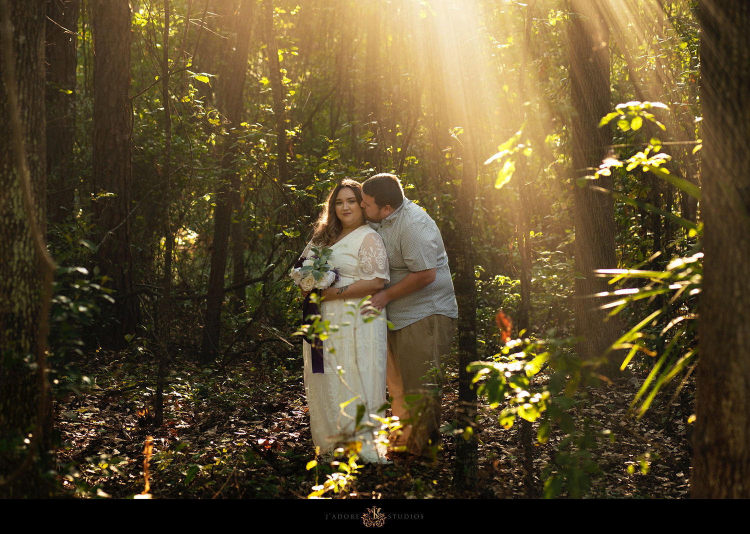 Groom kissing brides cheek in the woods in golden rays of light