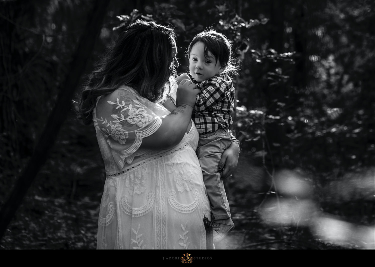 Black and white photo of Mother playing with son in golden light