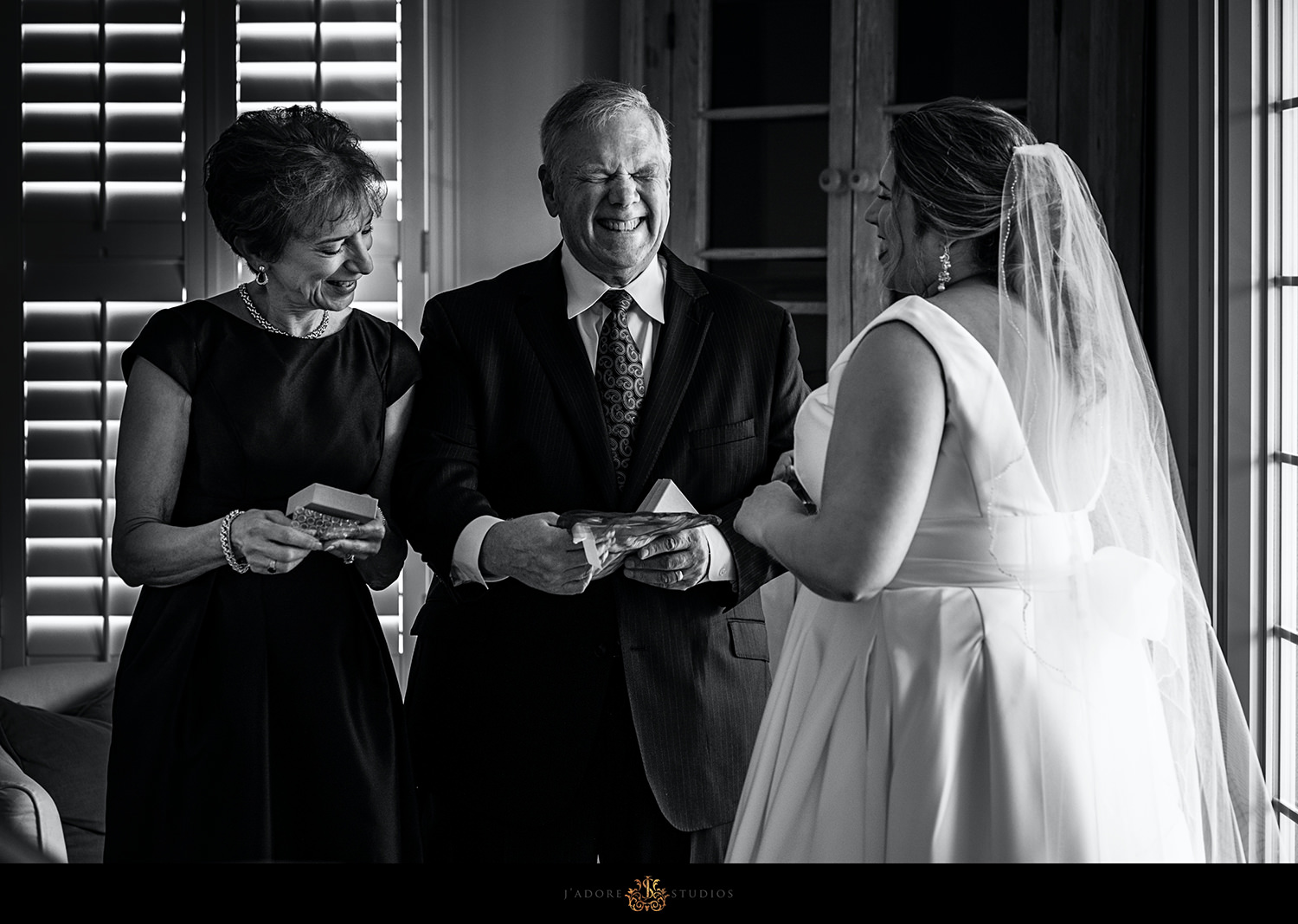 Bride laughing while giving parents gifts