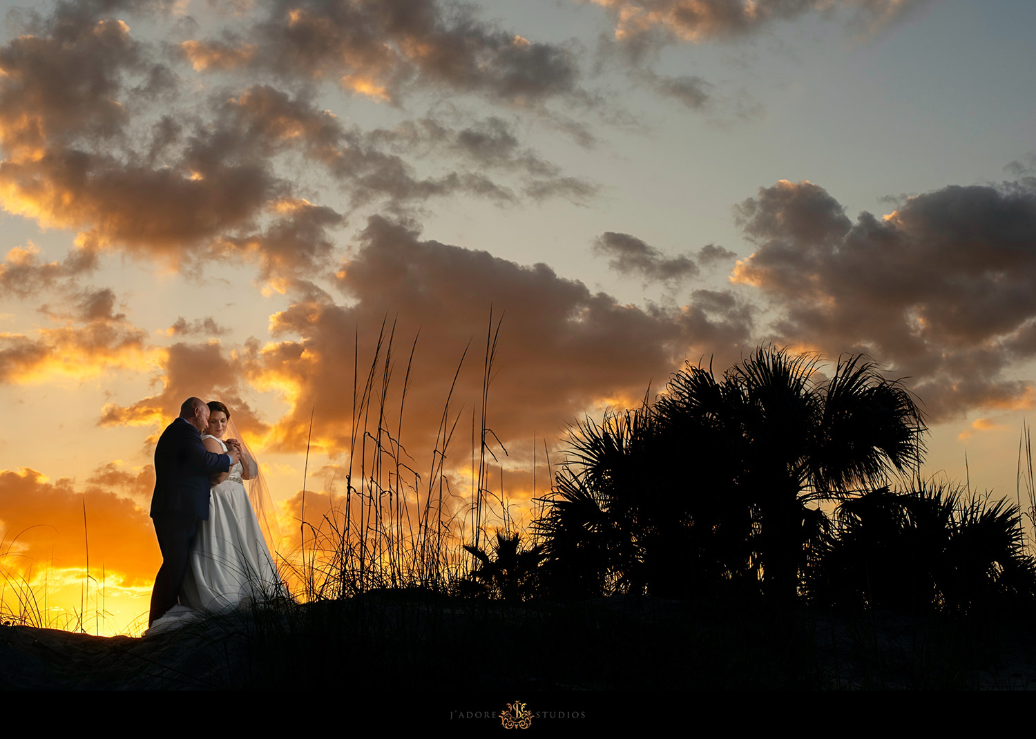 Bride and groom hugging at sunset with a beautiful sky