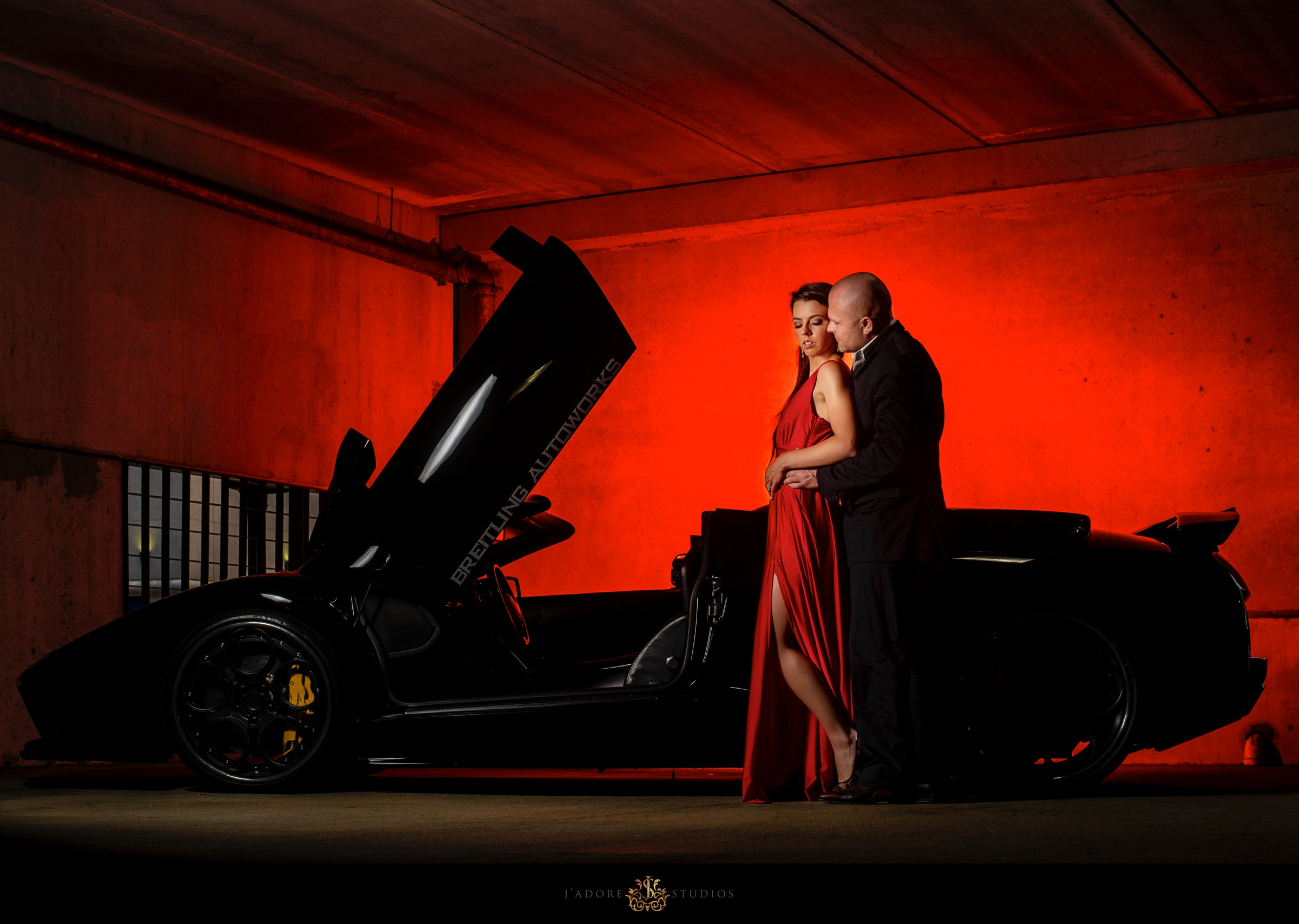 groom hugging bride in red dress in front of Lamborghini