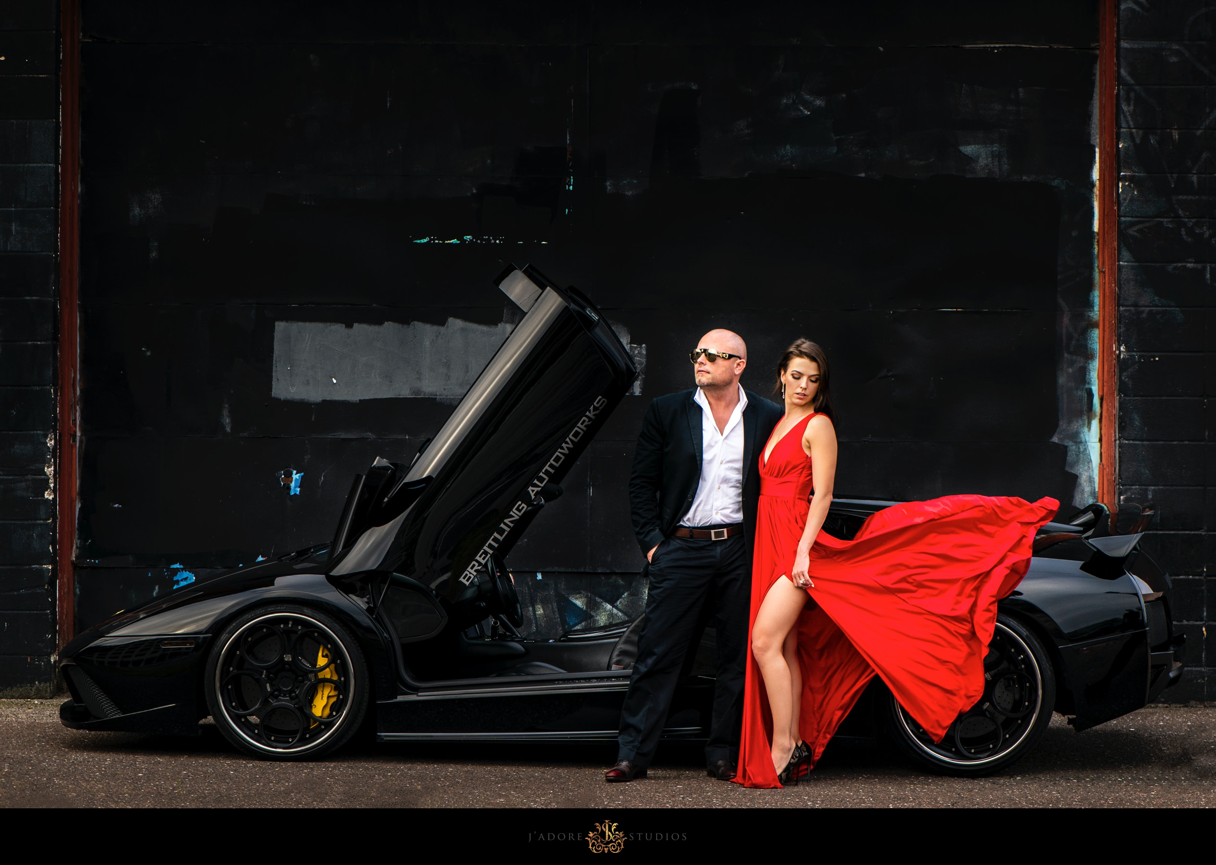 couple standing in front of lamoborghini.  bride in red dress