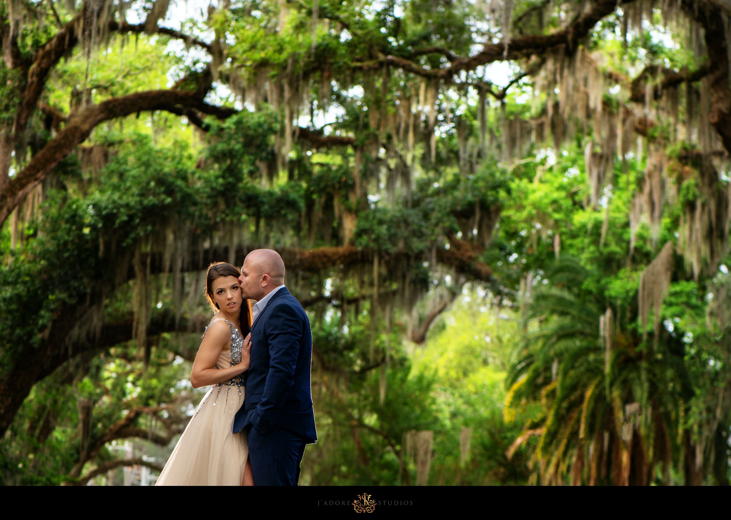 groom kissing brides cheek in mossy trees