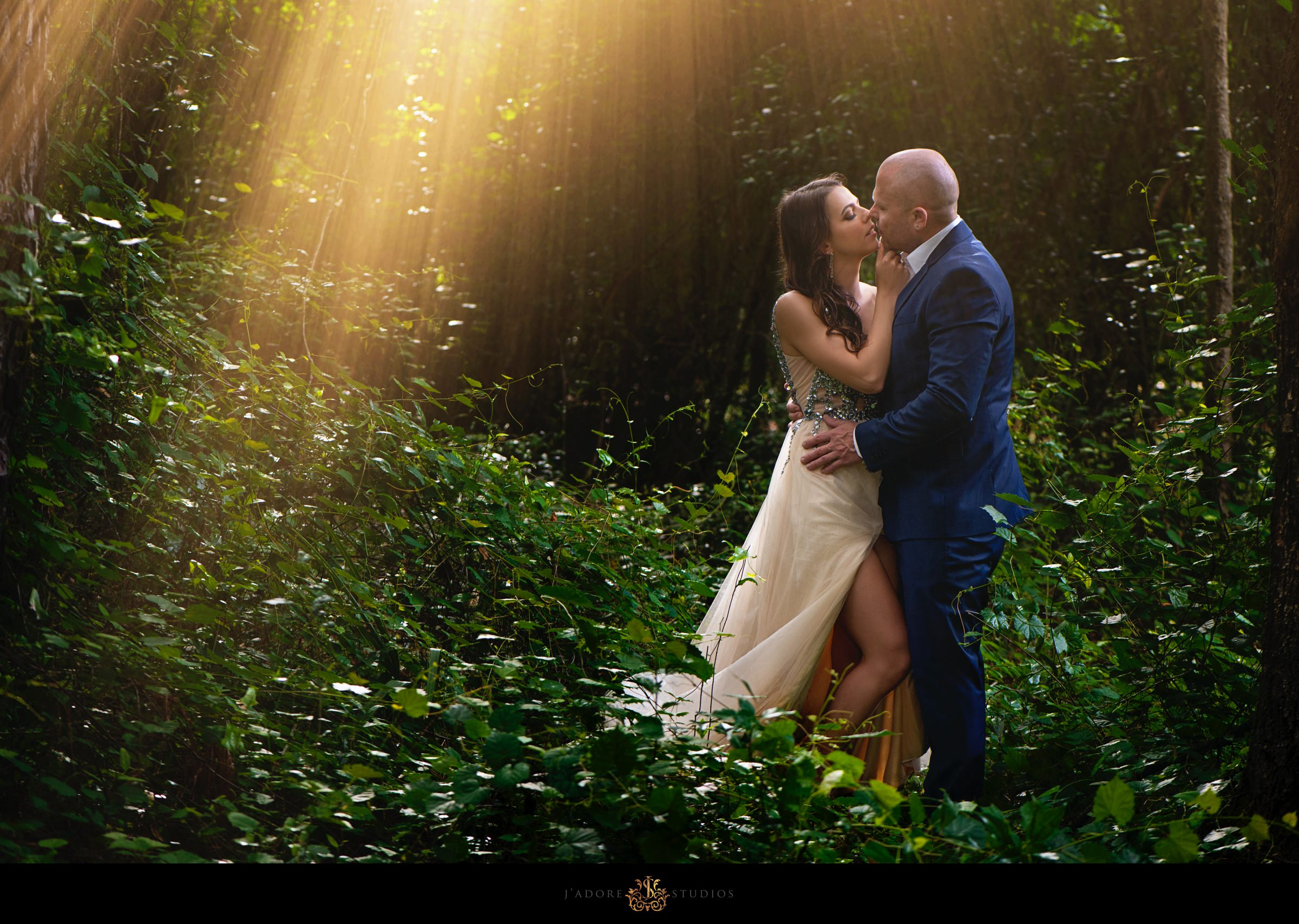 Couple kissing in the woods with sunshine ray on them