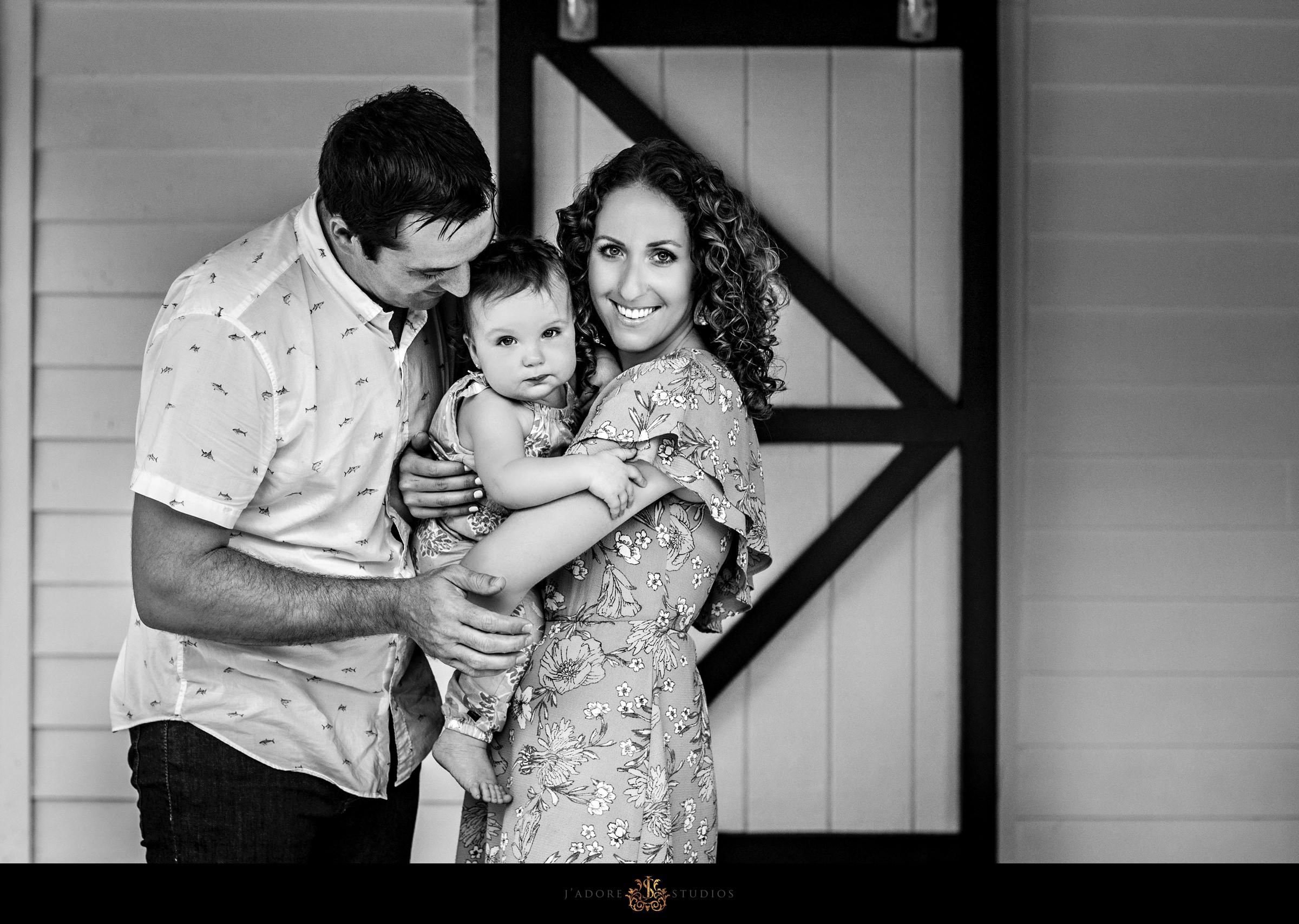 Family hugging in front of barn door