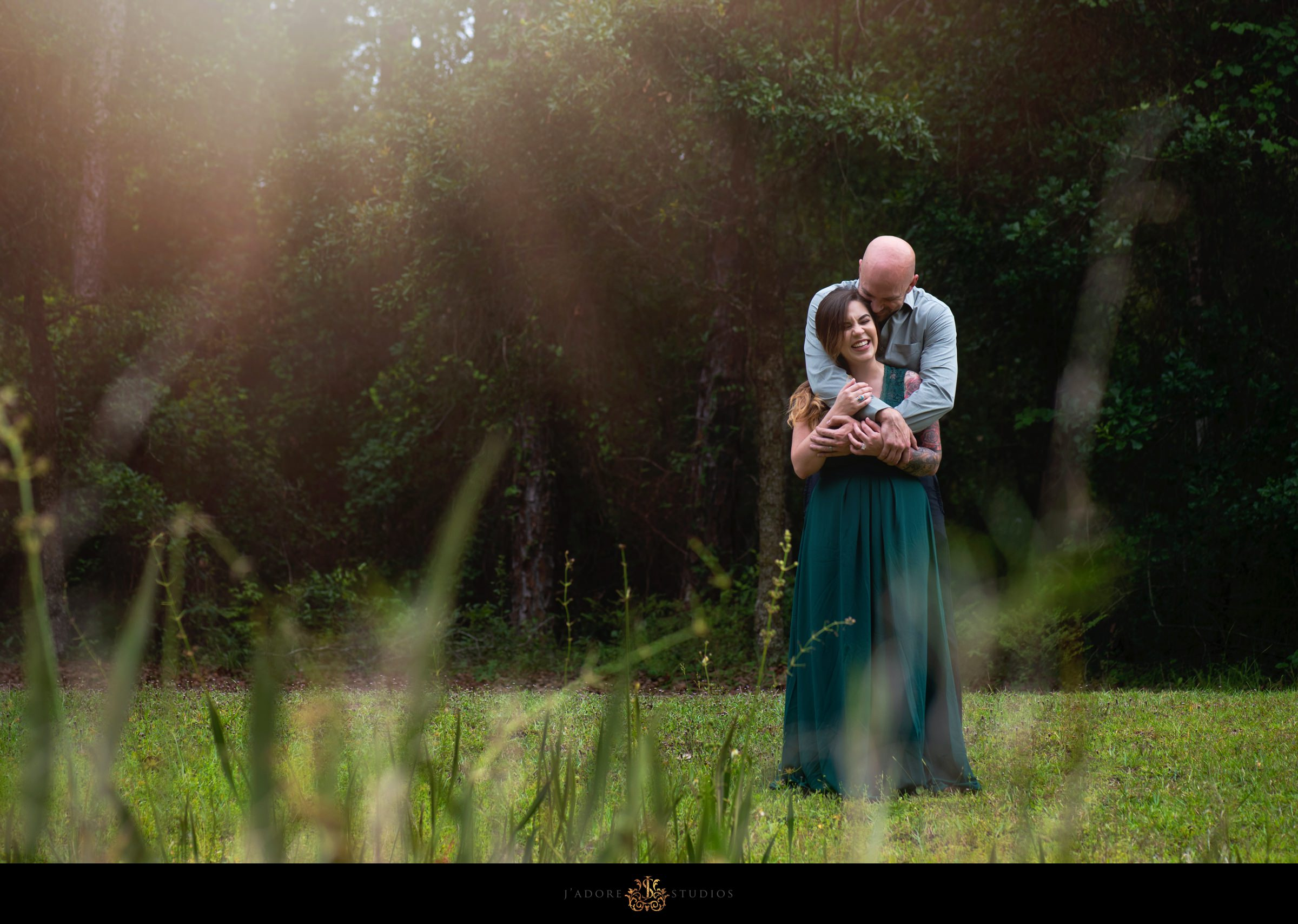 Husband hugging wife in front of pond at Alpine Grove Park
