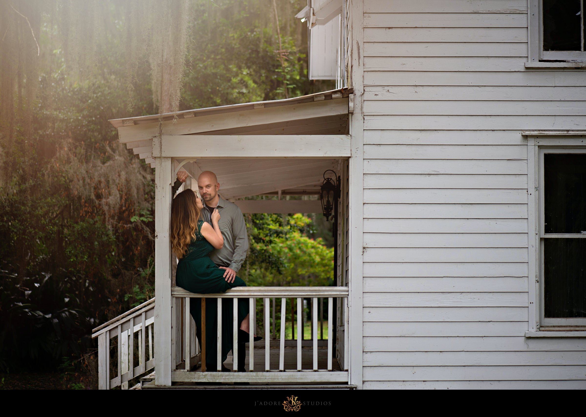 Wife hugging husband as he poses for the camera on the front porch of old house