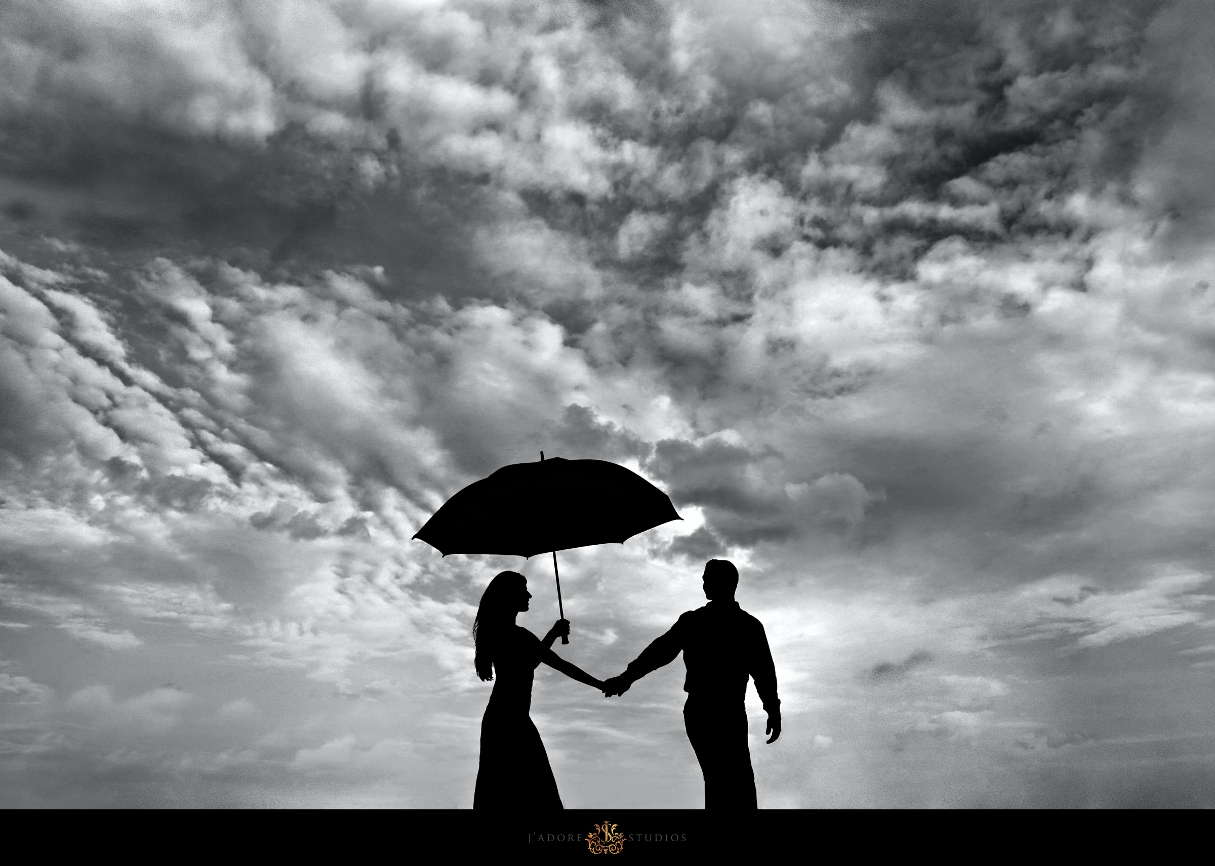 Black and White Silhouette photo of couple under an umbrella in front of cloudy rainy sky at Oyster Bay Yacht Club