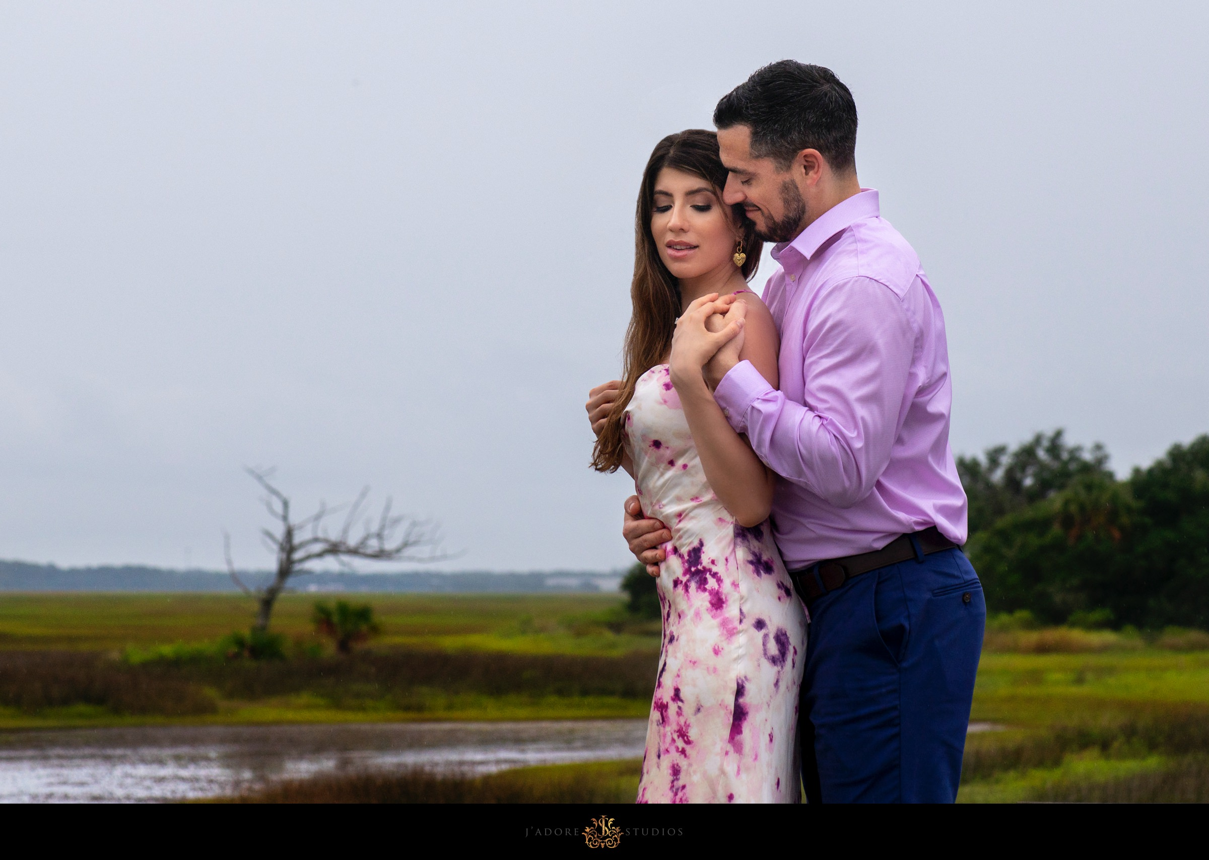 Couple hugging in front of marsh in Amelia Island