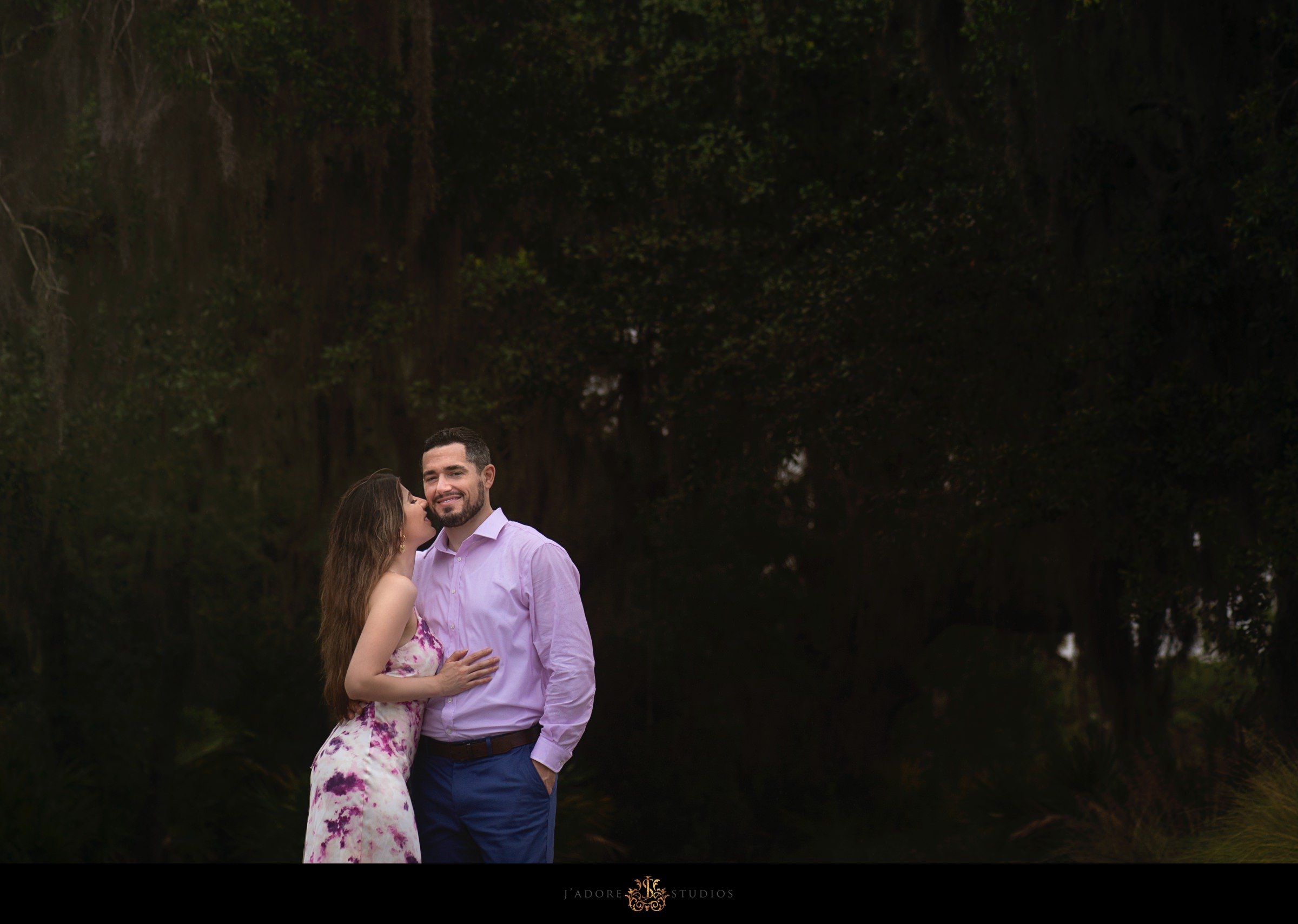 Bride kissing grooms cheek in front of mossy trees in Amelia Island Florida