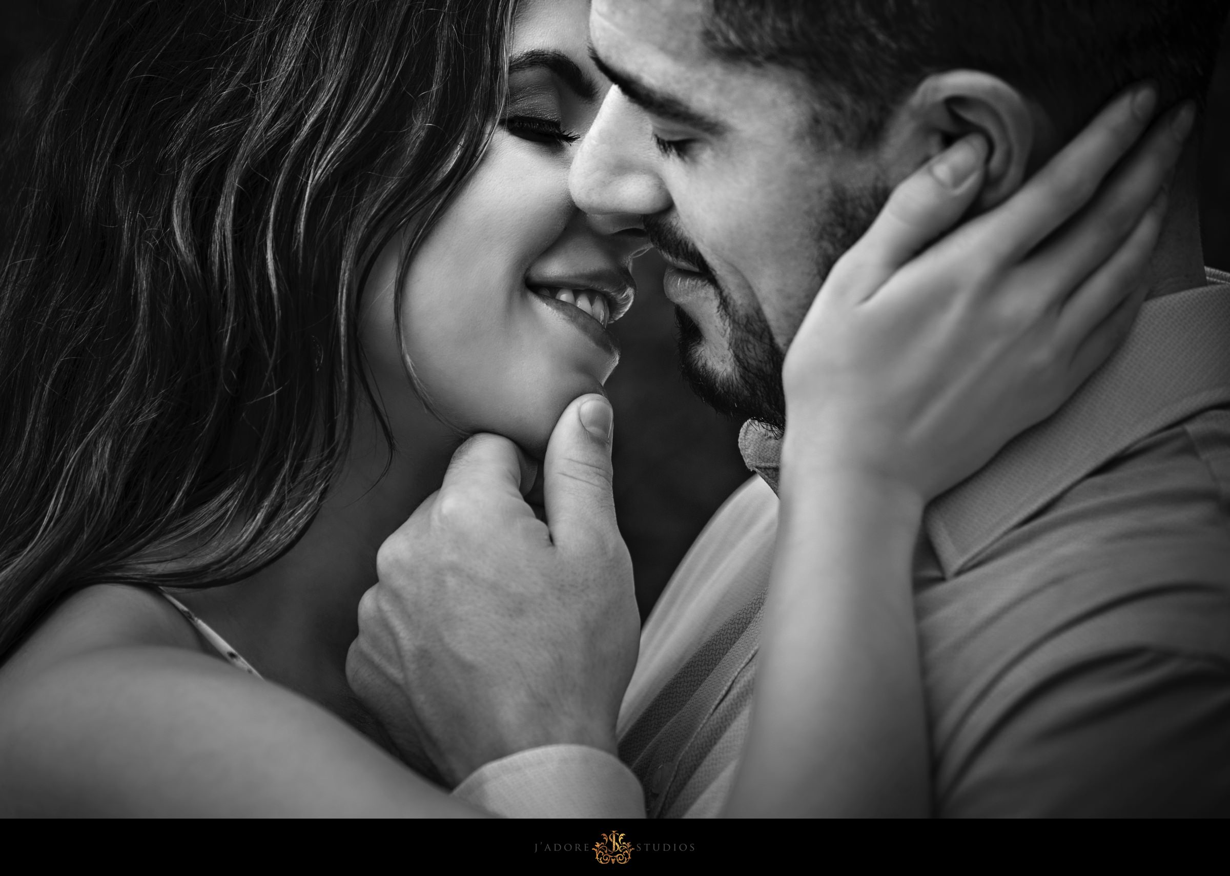 Black and white close up photo of couple holding each other and almost kissing