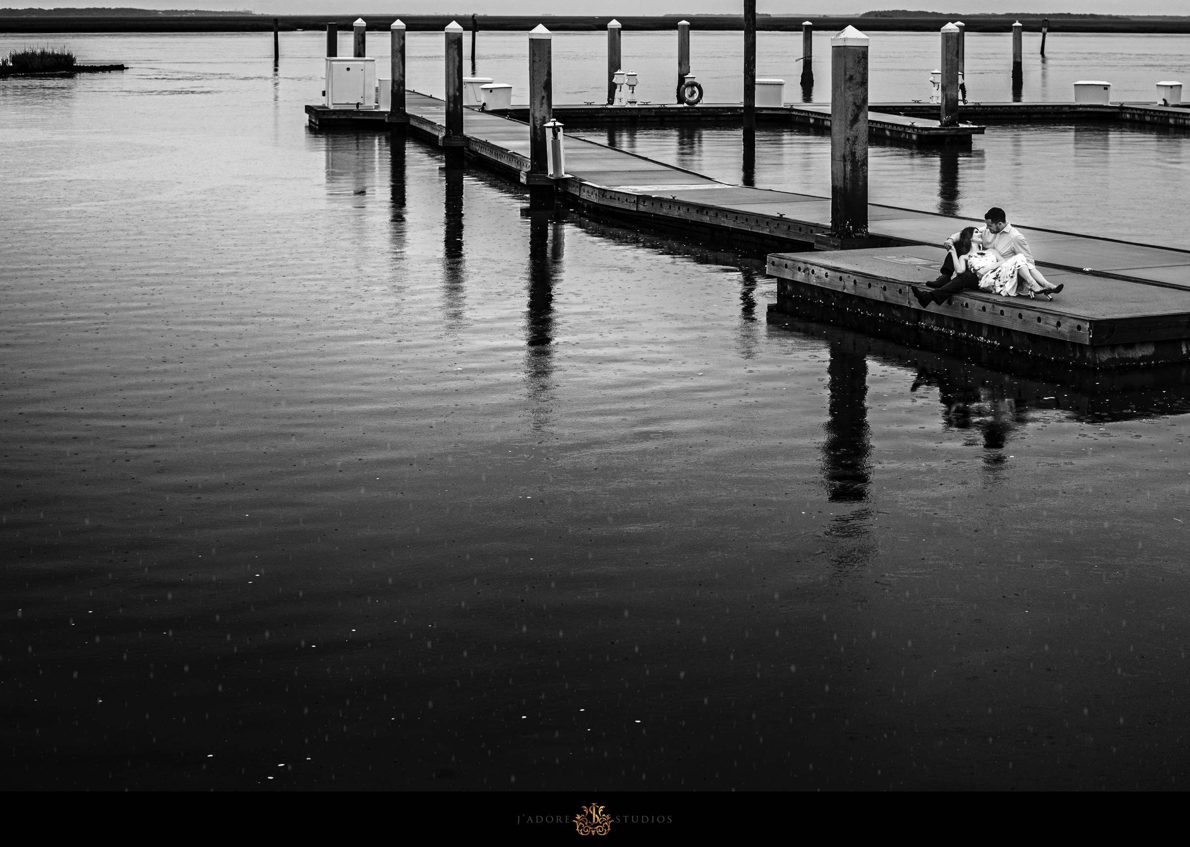 Back and white photo of couple laying on dock at Oyster Bay Yacht Club in Amelia Island Florida