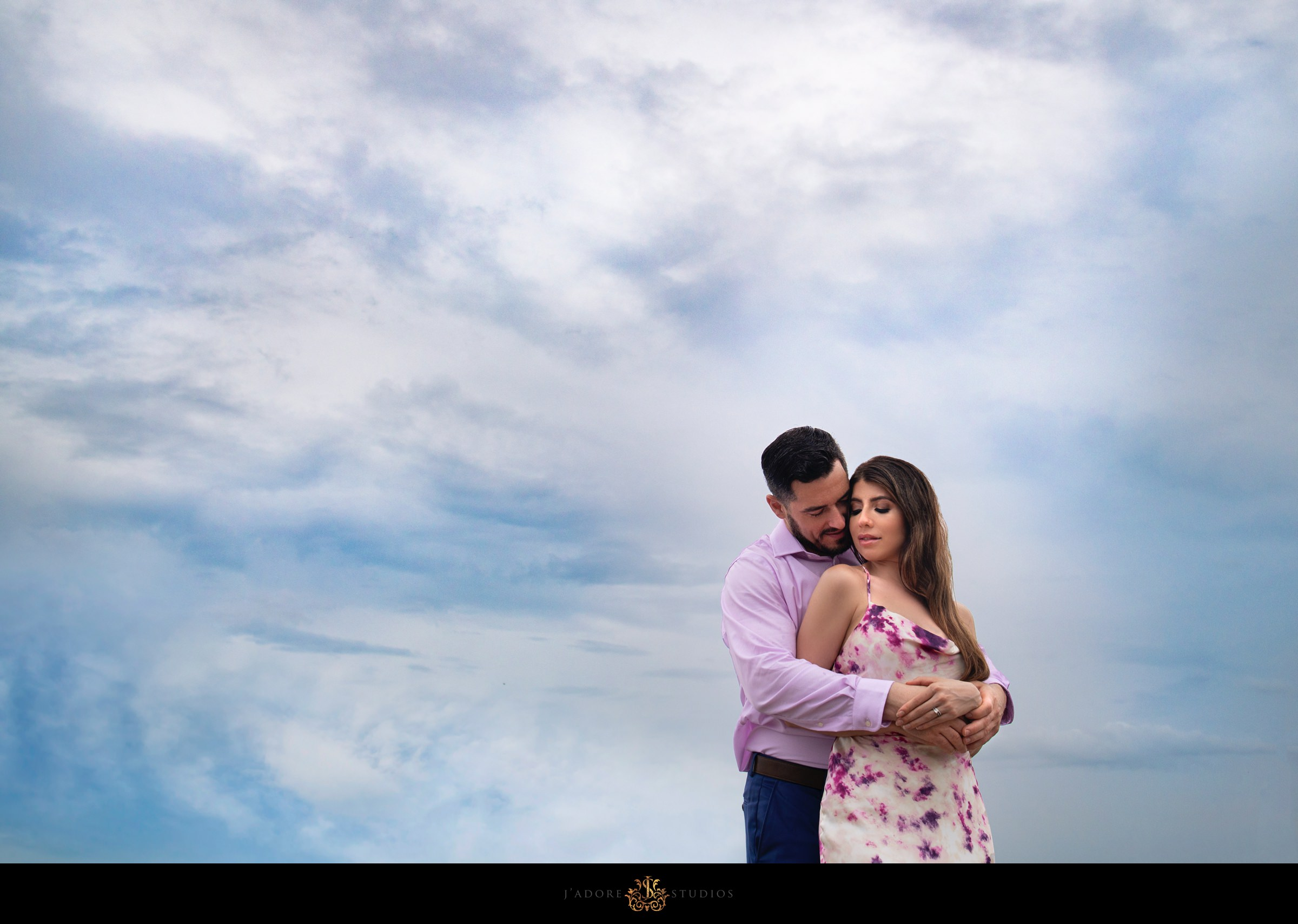 Couple snuggling under a cloudy blue sky at Oyster Bay Yacht Club