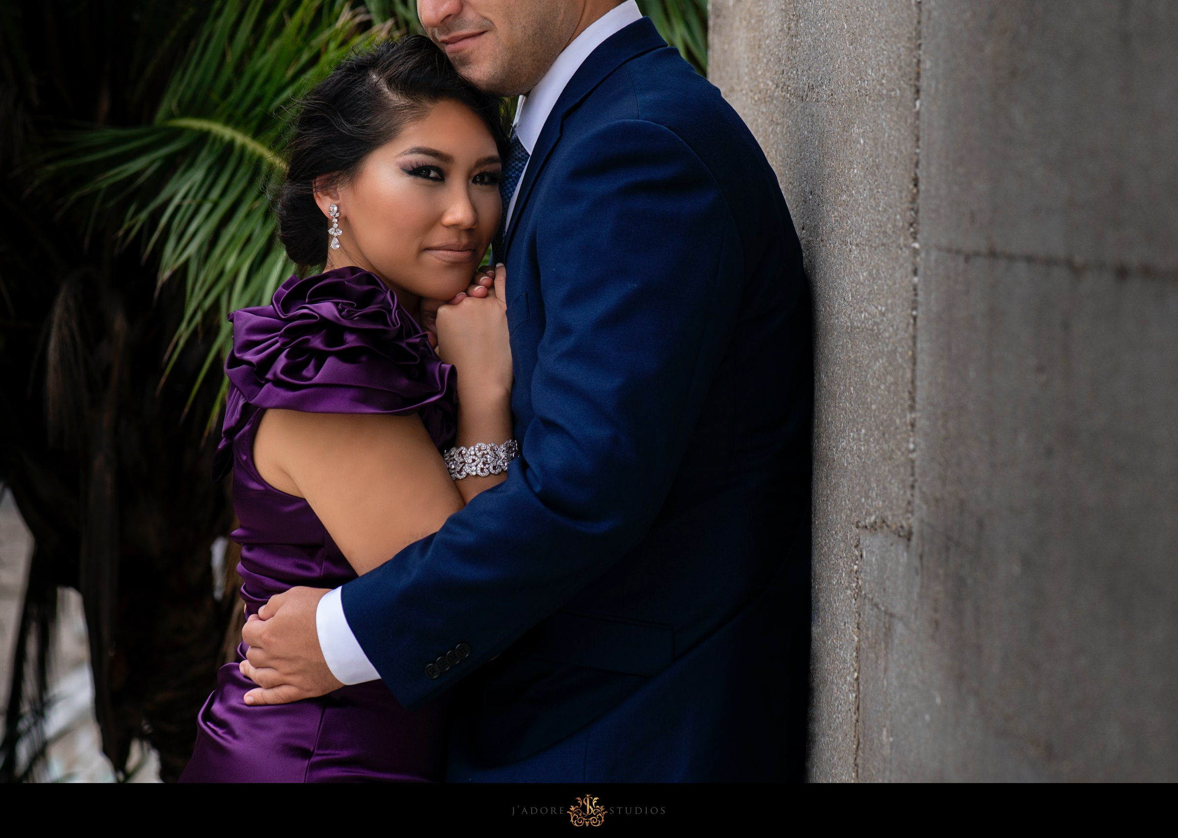 woman in purple formal gown hugging her husband in front of lightner museum wall in saint Augustine Florida
