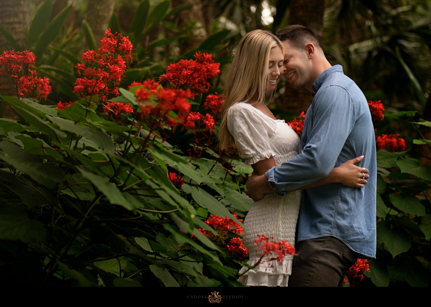 Groom to be kissing bride to be's cheek near red flowers