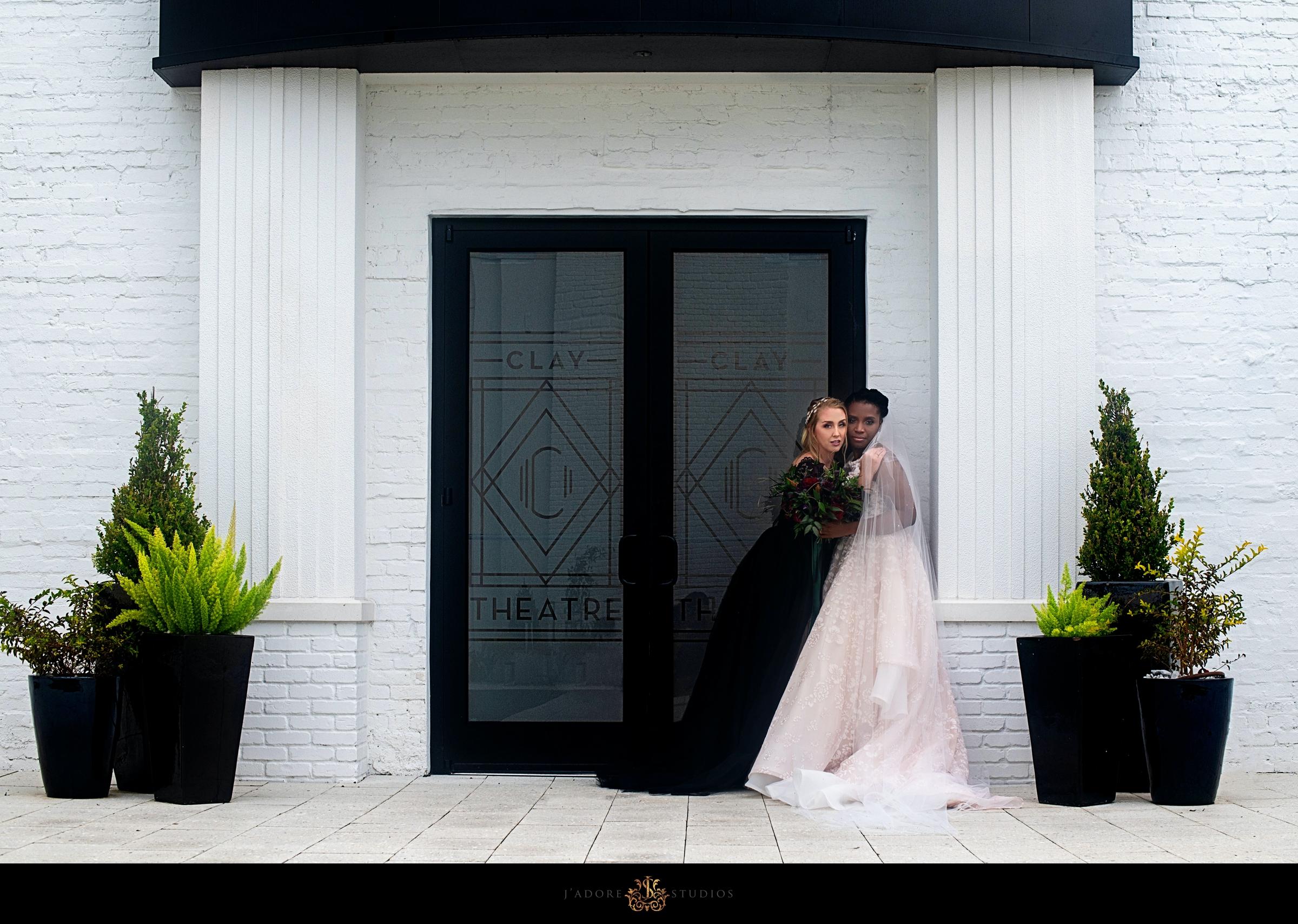 Bride and Bride hug in Clay Theatre courtyard