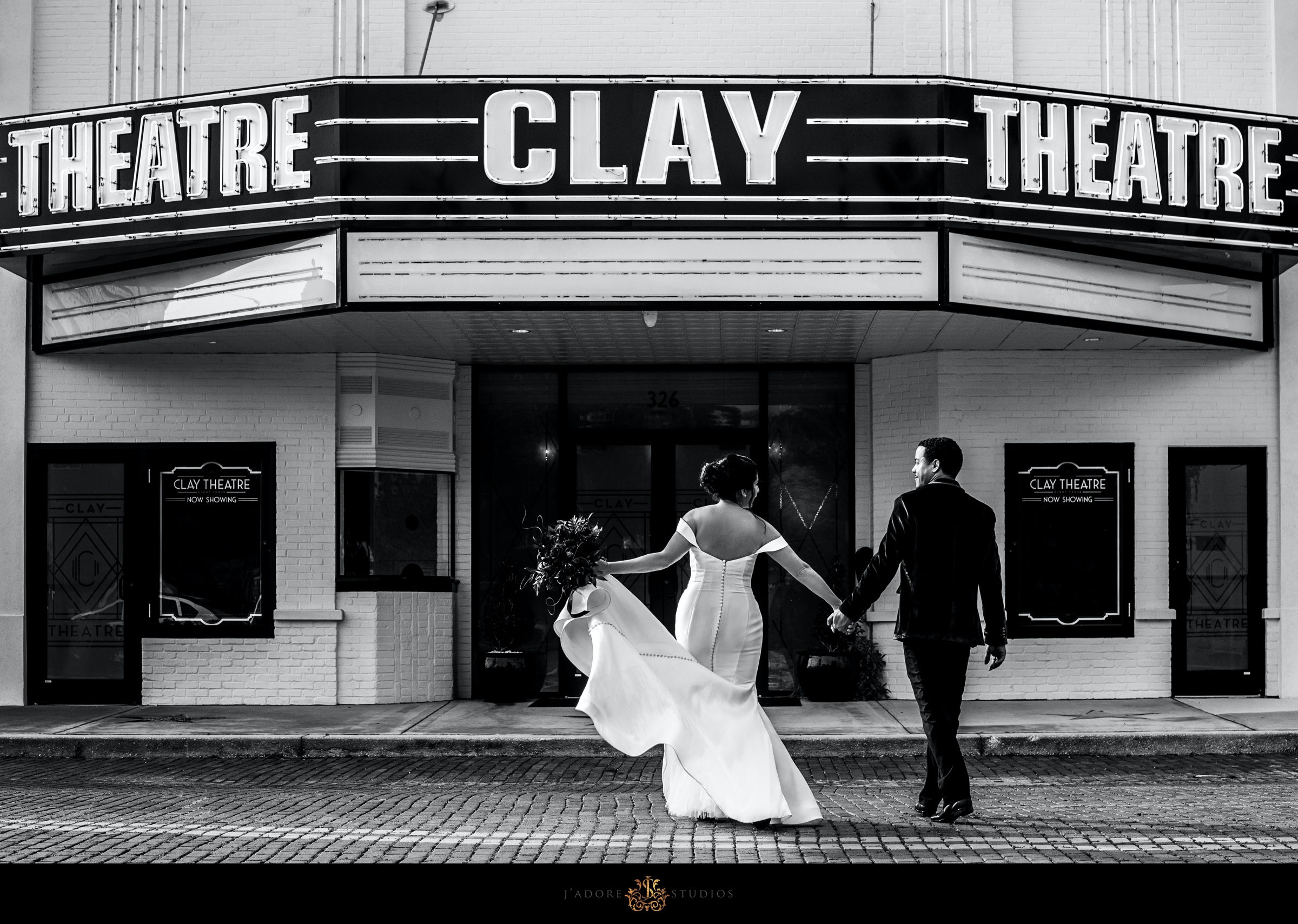Bride and groom walk on brick road in front of the marquee at the Clay Theatre