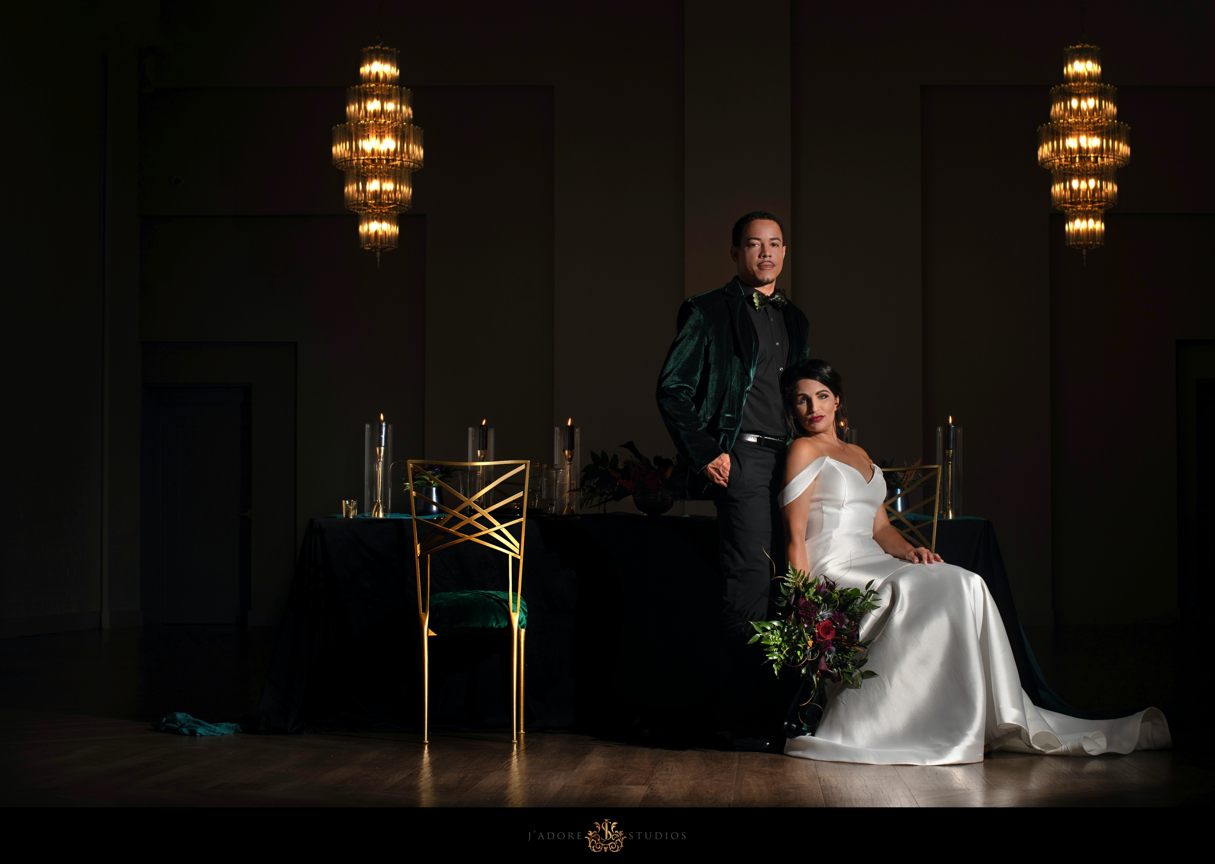 Couple posing in front of head table in the ballroom at the Clay Theatre