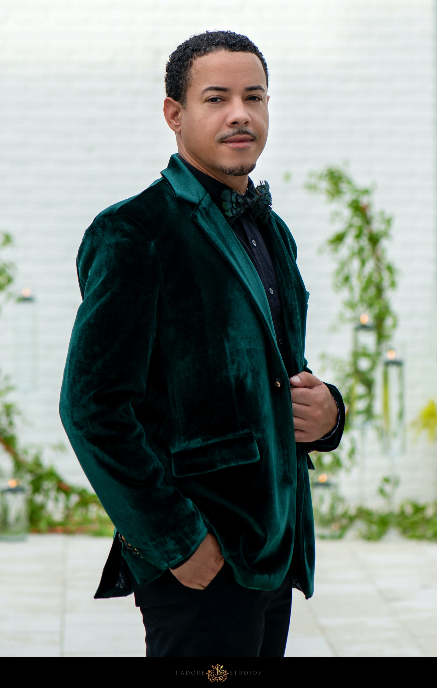 Groom in green jacket poses at Clay Theatre
