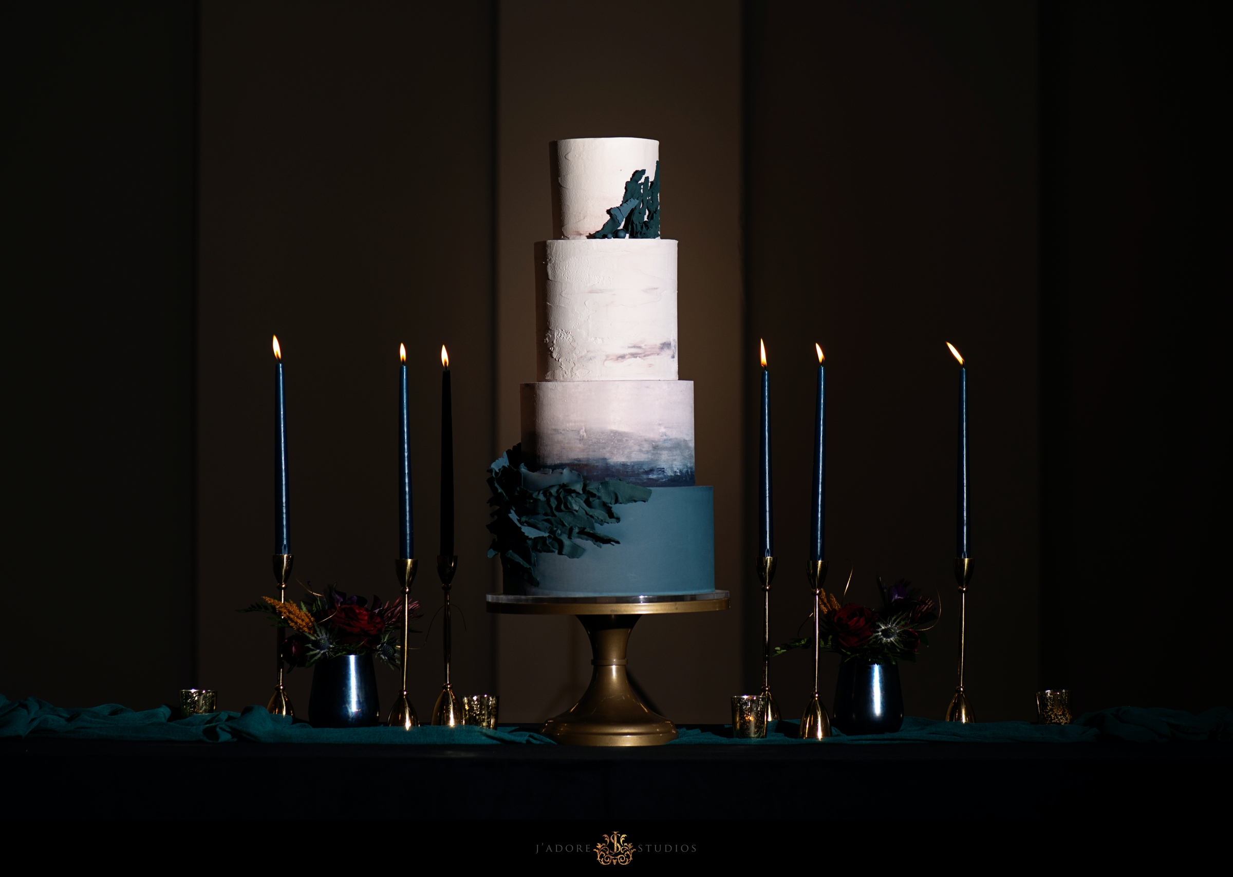 Teal and white cake with black candles at the Clay Theatre in Jacksonville Florida