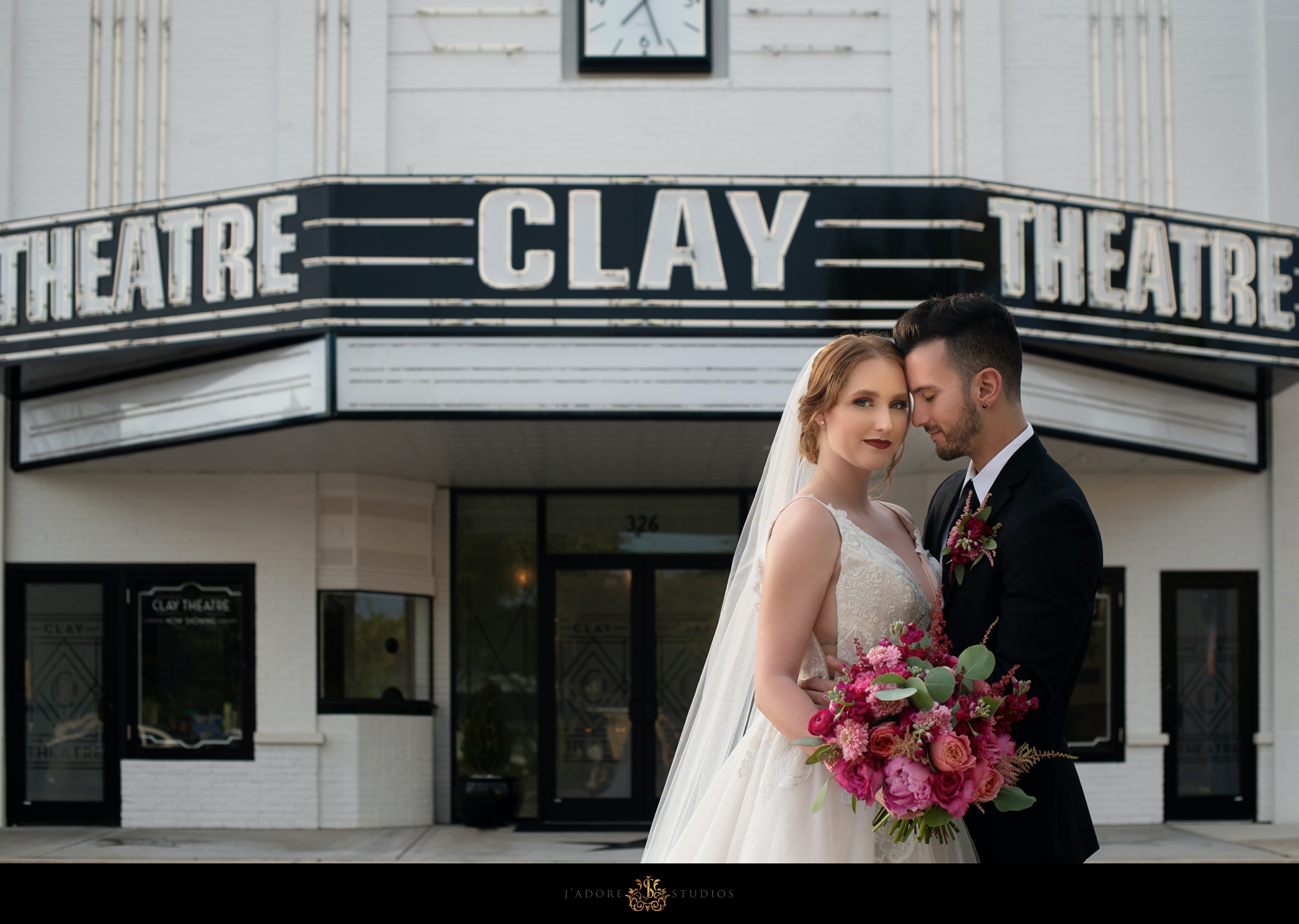 Groom hugging bride in front of marquee at Clay Theatre Jacksonville