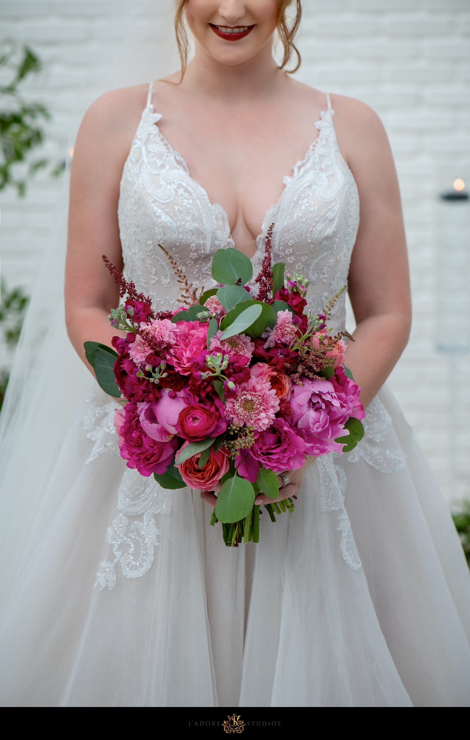 Bride wearing Miss Hayley Paige gown holding pink bouquet