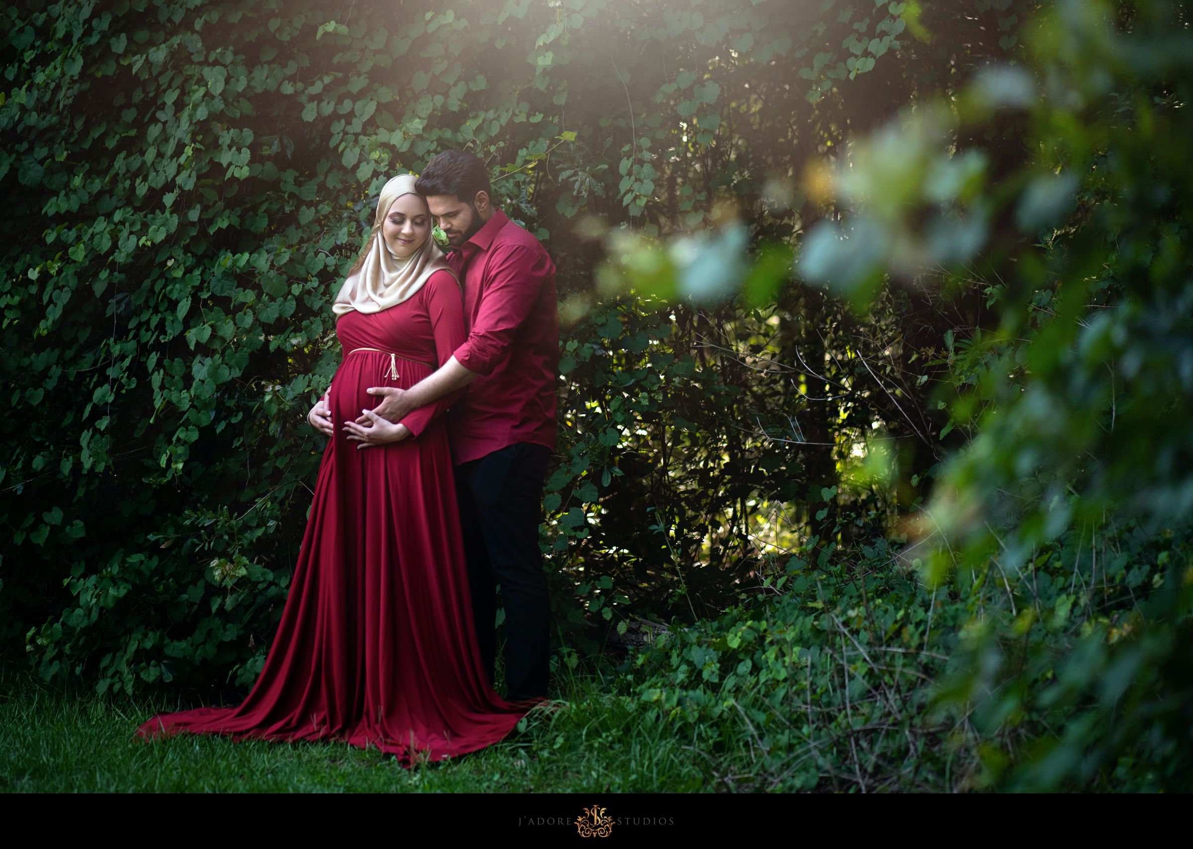 Husband hugs pregnant wife in red dress and hijab in park in Jacksonville Florida