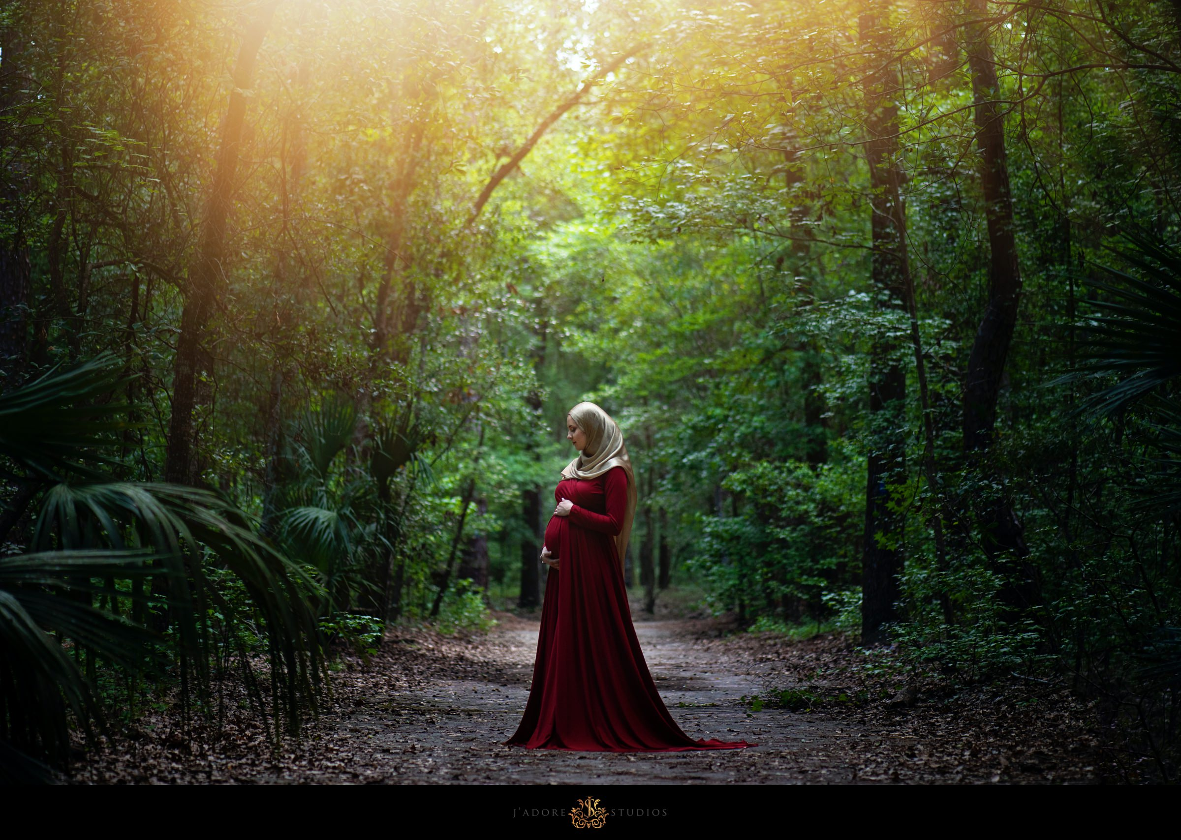 Pregnant woman in red dress in a forest in Jacksonville Florida