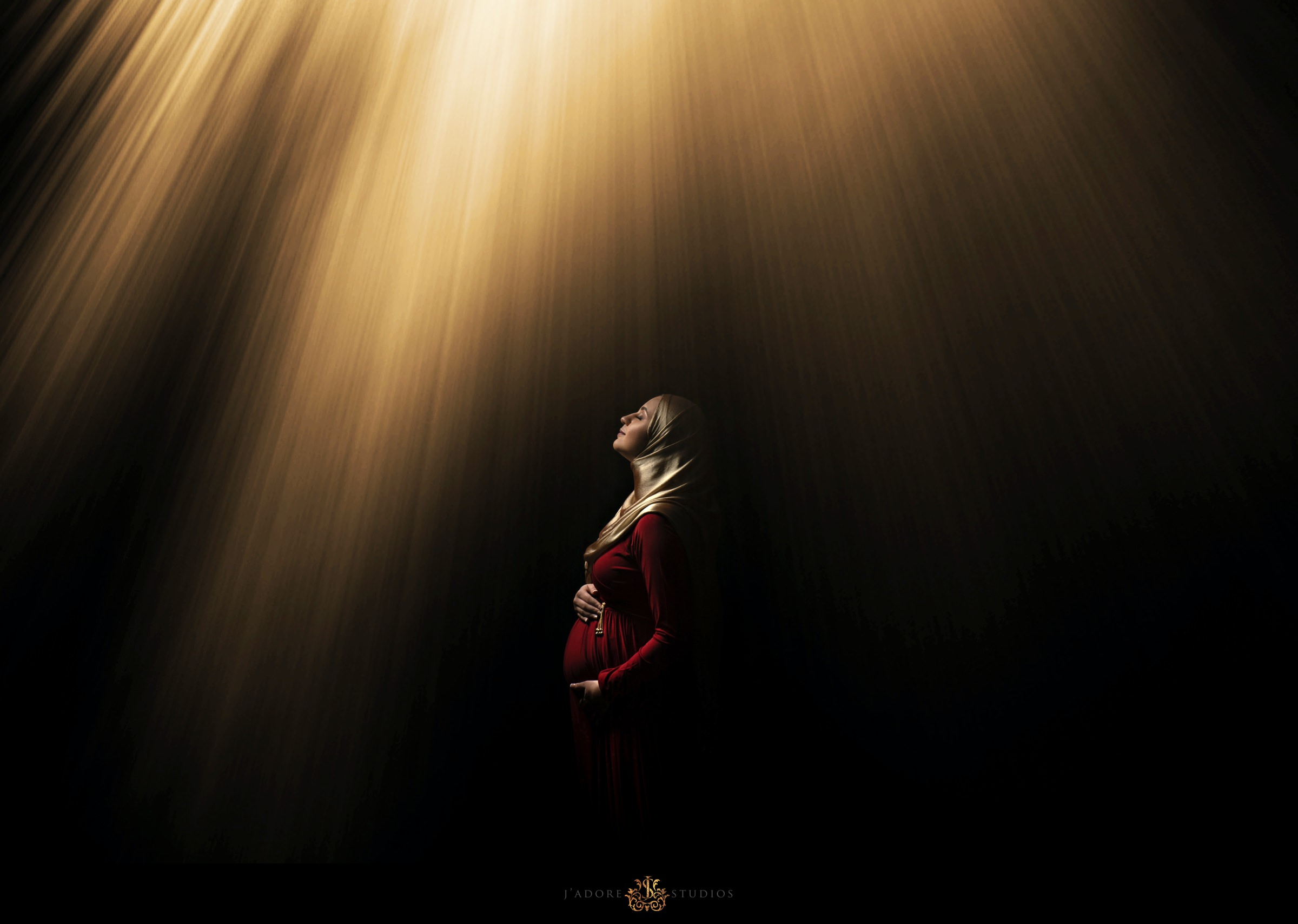 Pregnant woman in red dress and hijab poses in front of black wall under rays of sunshine in Jacksonville Florida