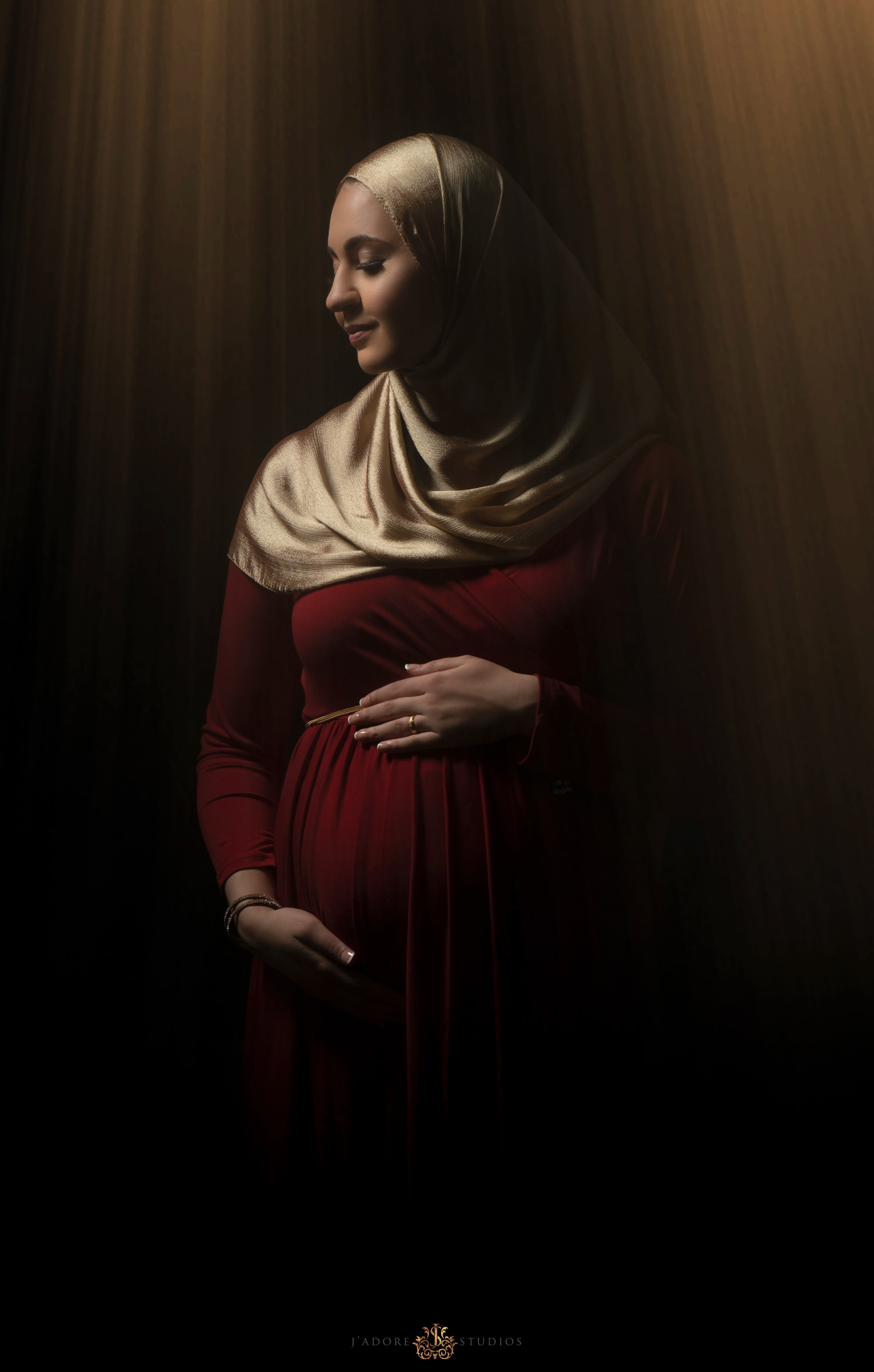 Pregnant woman wearing red dress in ray of sunshine in front of black wall