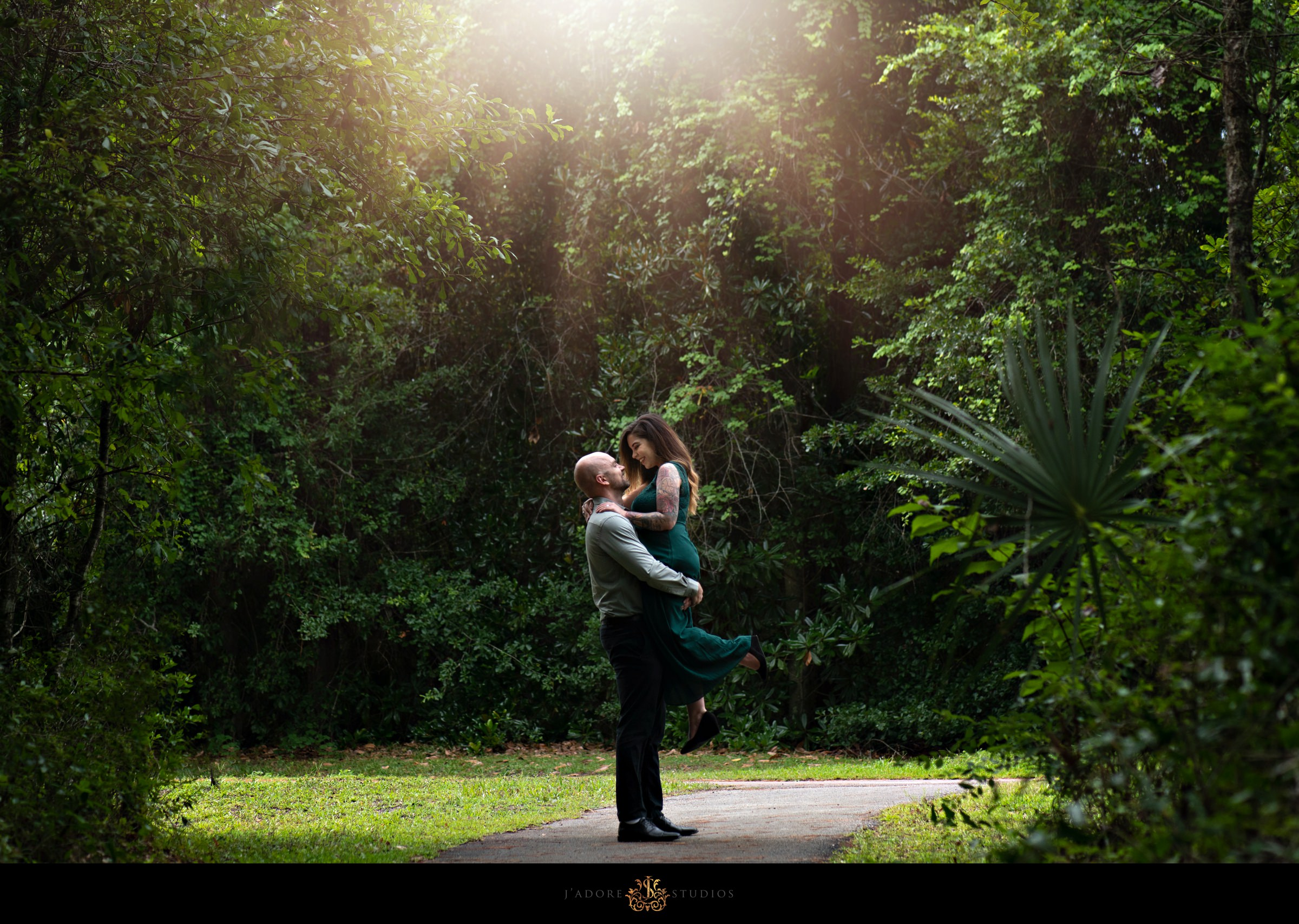Husband picking up wife in front of green ivy with rays of sunshine at Alpine Grove Park