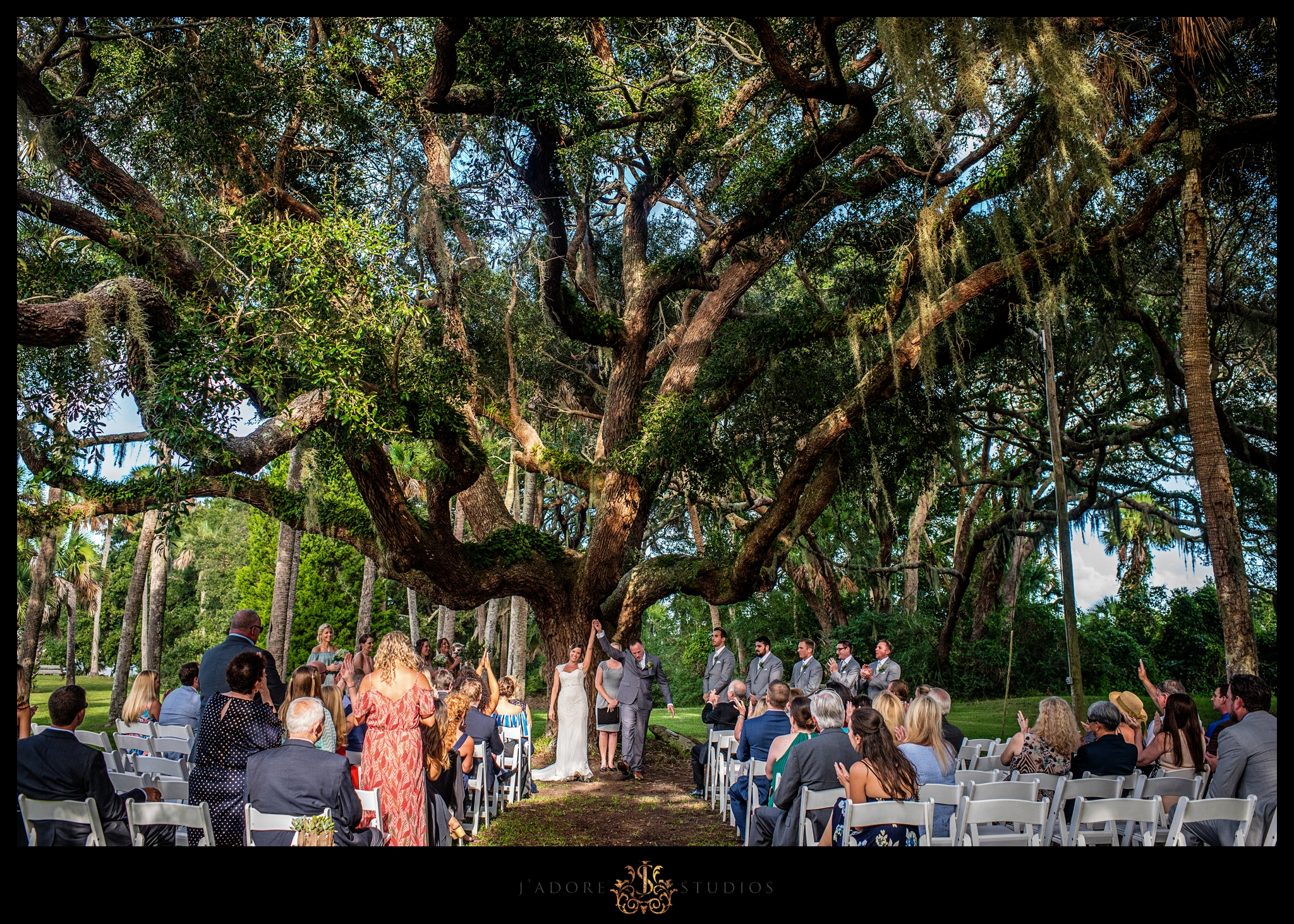 Ceremony photo of couple under big oak tree at the Ribault Club