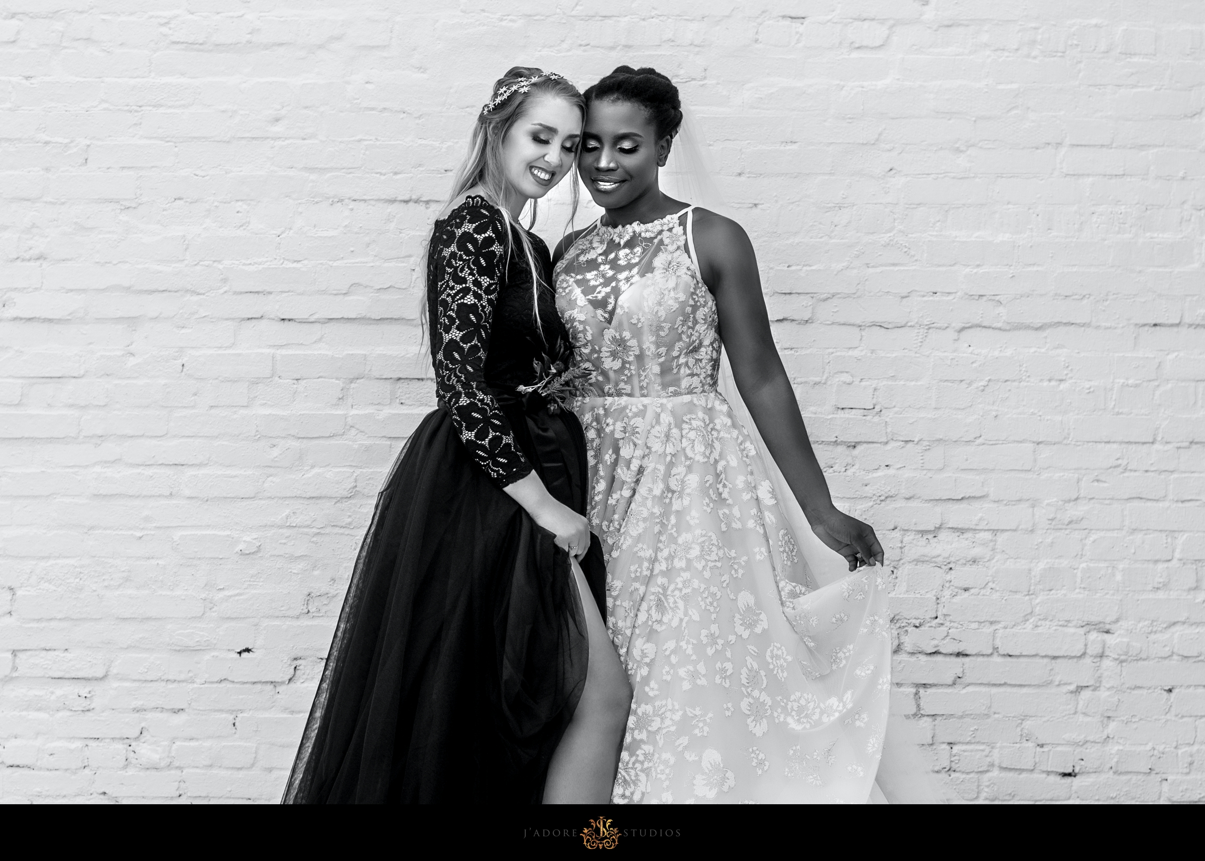 Two brides hug in front of brick wall at Clay Theatre in Jacksonville Florida