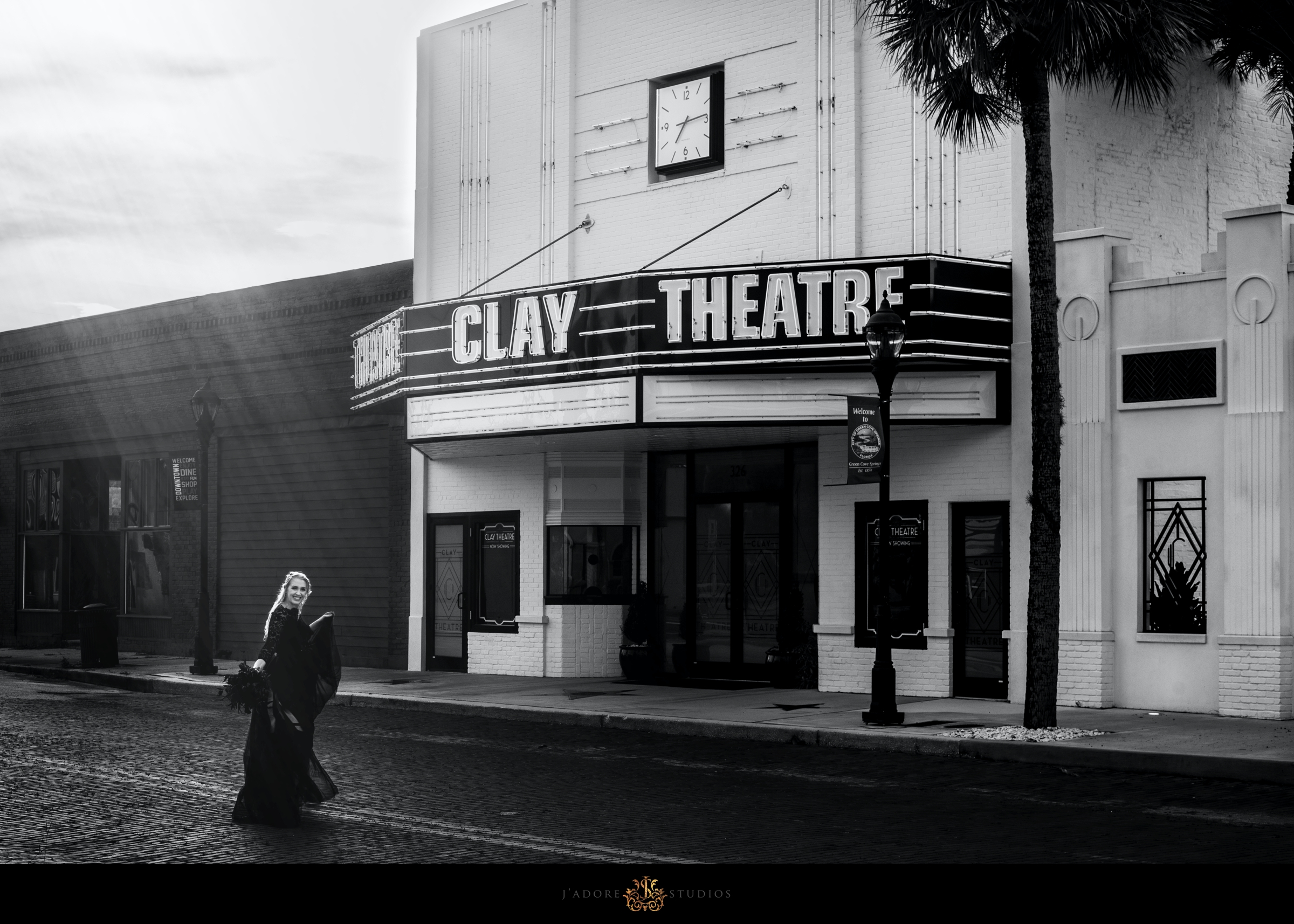 Bride runs on cobblestone street in front of Clay Theatre in Green Cove Springs Florida