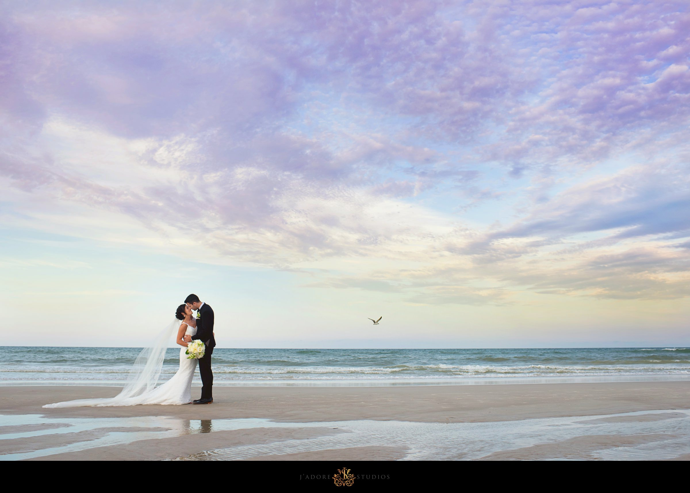 Couple kissing on the beach with a sunset sky at the Casa Marina in Jacksonville Beach