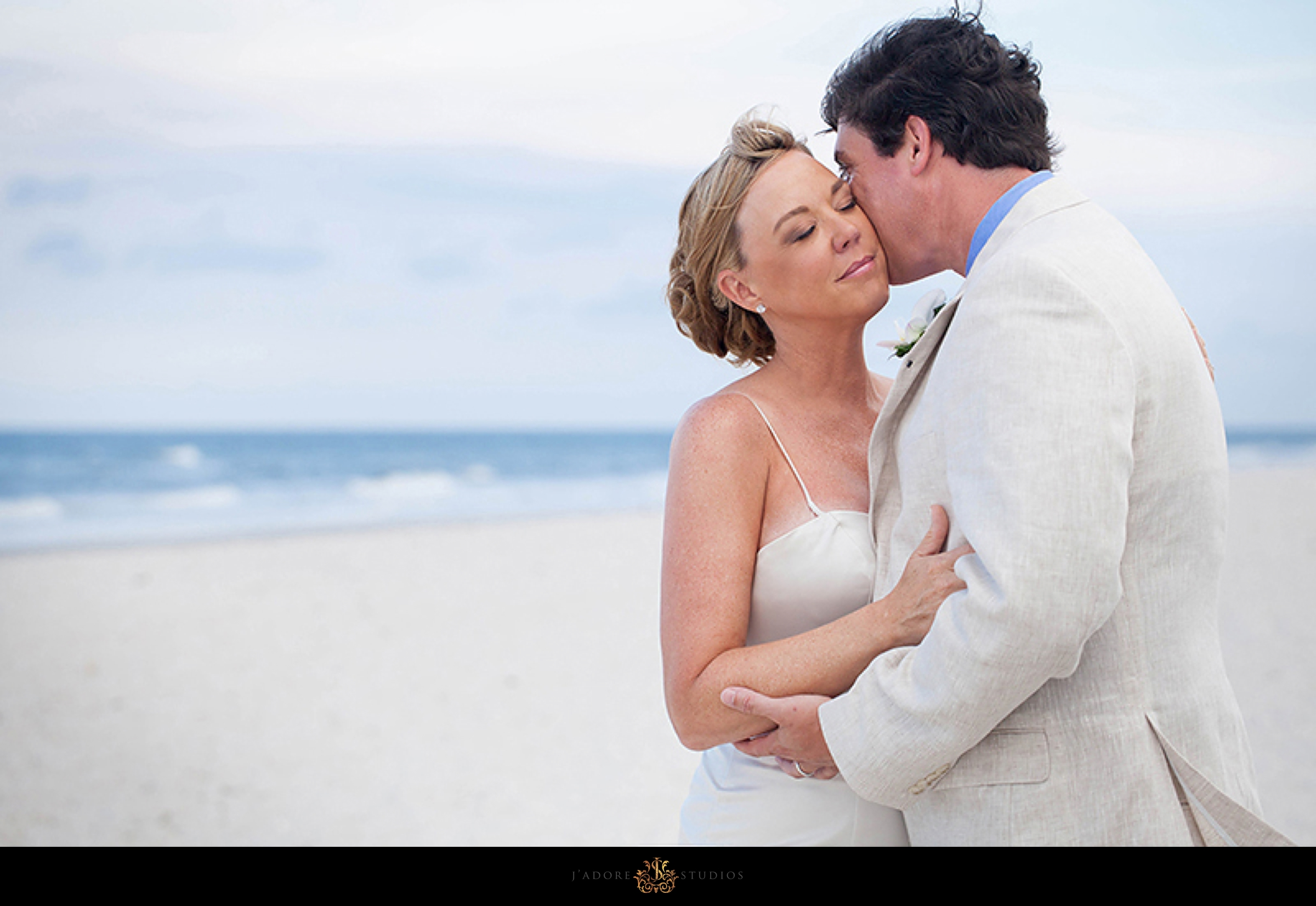 Groom kissing brides cheek on the beach at the Ponte Vedra Inn and Club