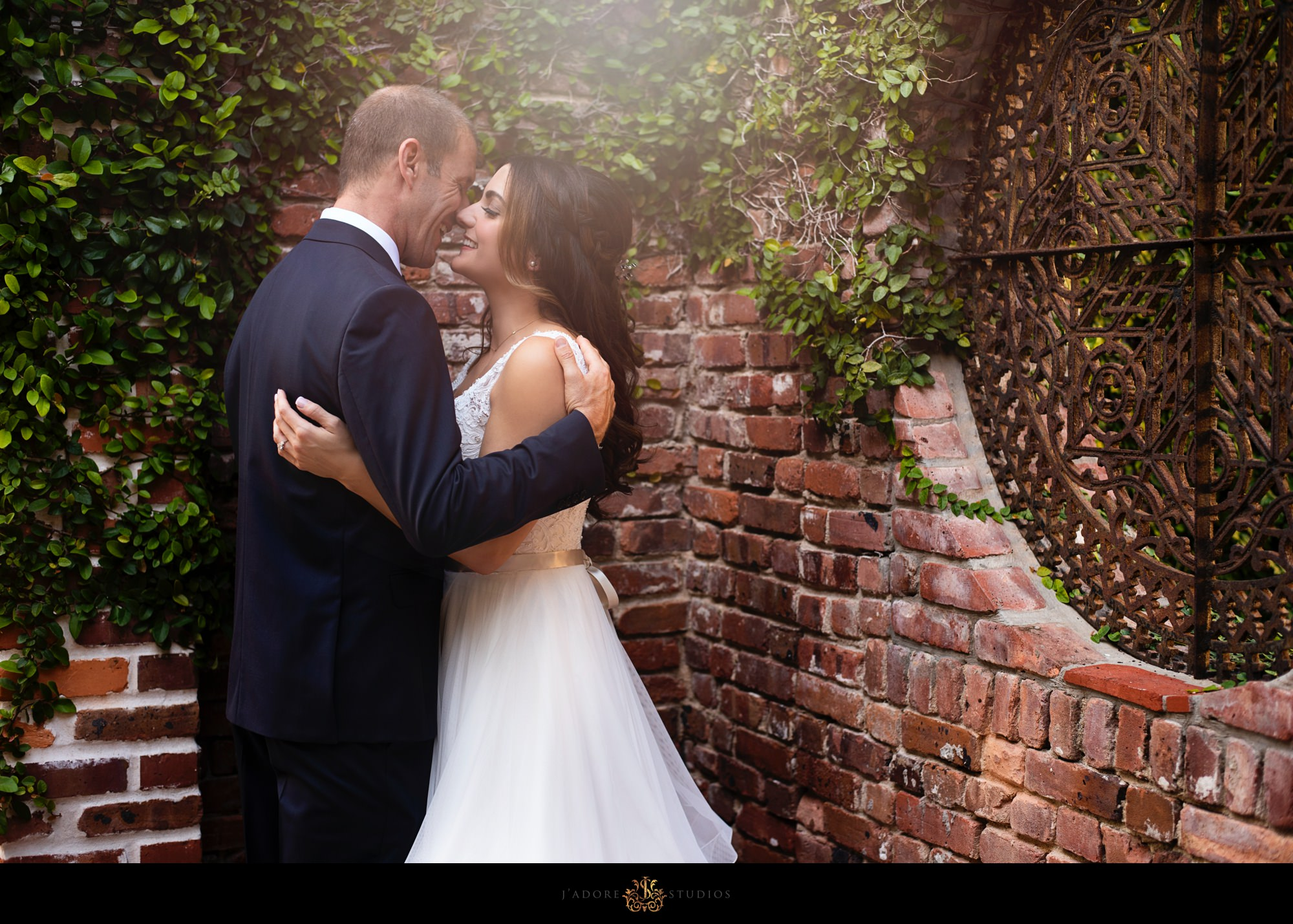 Couple kissing in front of brick wall at lightner museum in Saint Augustine florida
