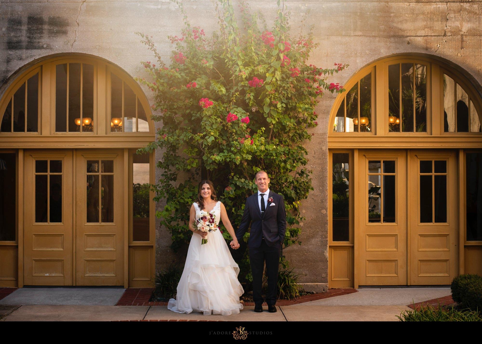 bride and groom holding hands in front of lightner museum Saint Augustine Florida