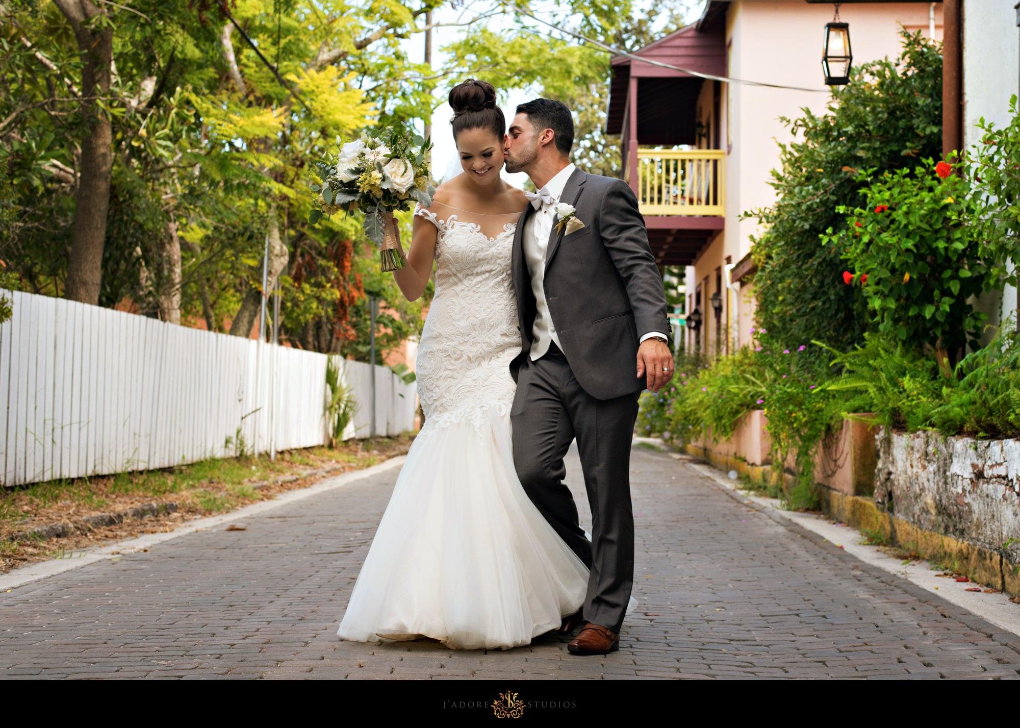 groom kisses bride on cheek walking on streets of Saint Augustine Florida