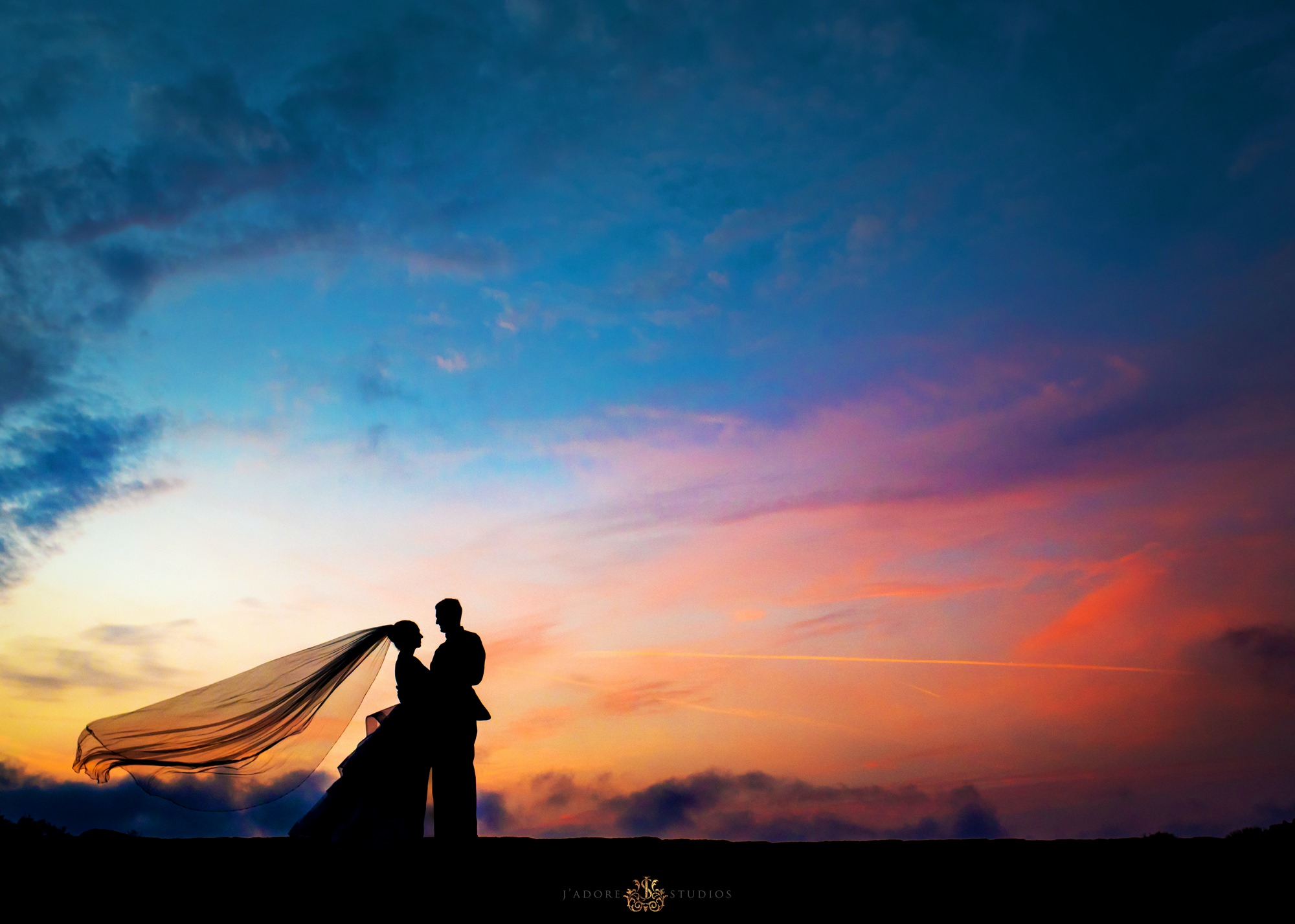 silhouette sunset photo of couple with brides veil in the wind - treasury on the plaza Saint Augustine Florida