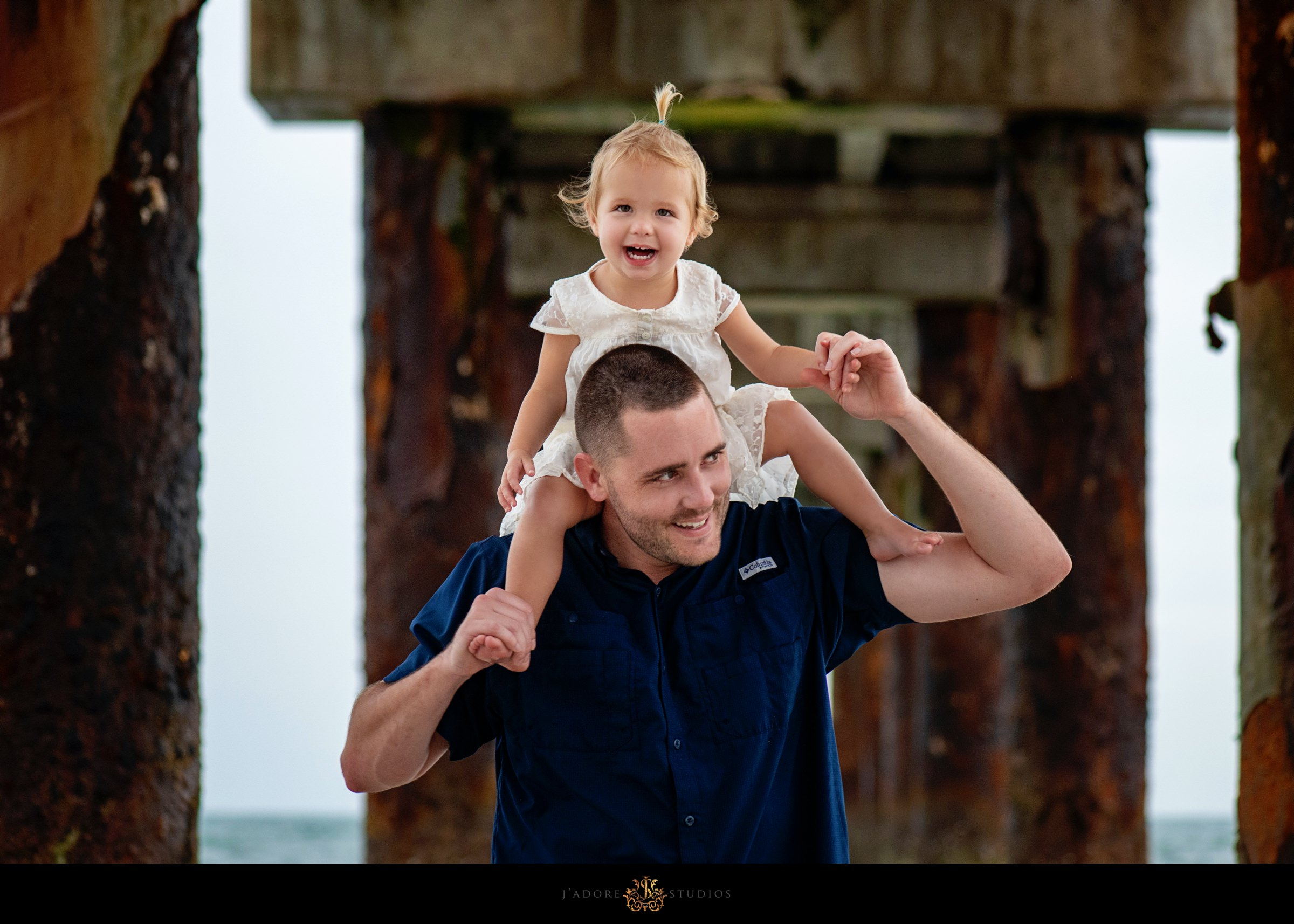 Little girl sitting on her fathers shoulders under the Saint Augustine Pier
