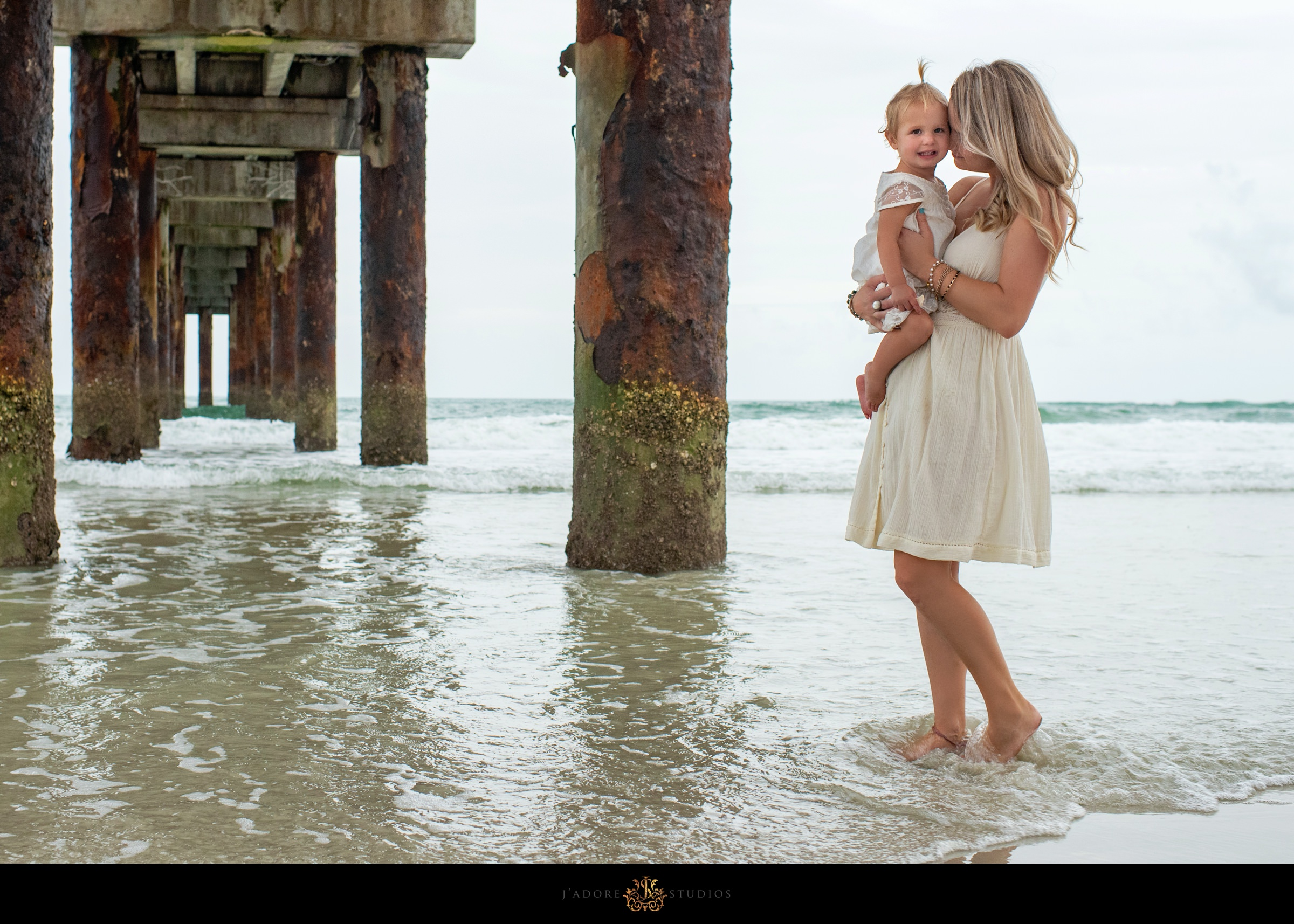 Mother kissing daughters cheek at the Saint Augustine Pier in Florida